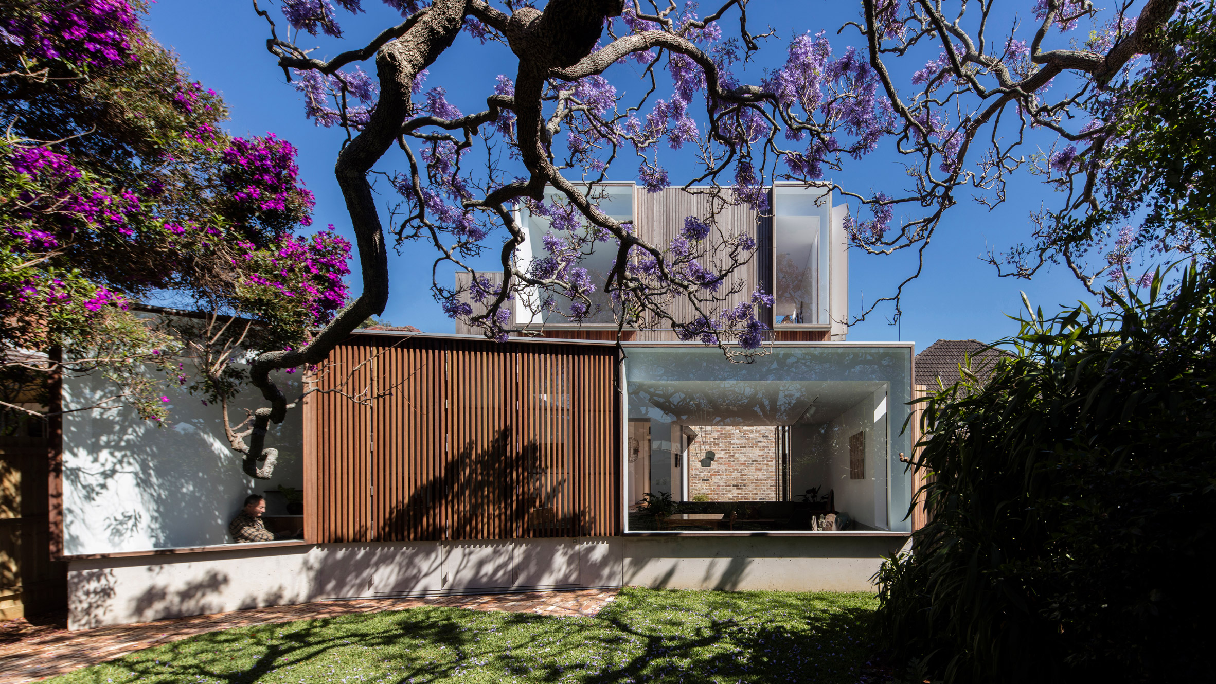 Shot of back of house, which is made up of stacked concrete boxes with large picture windows and a slatted wall. A large blooming tree's branches extend toward it.