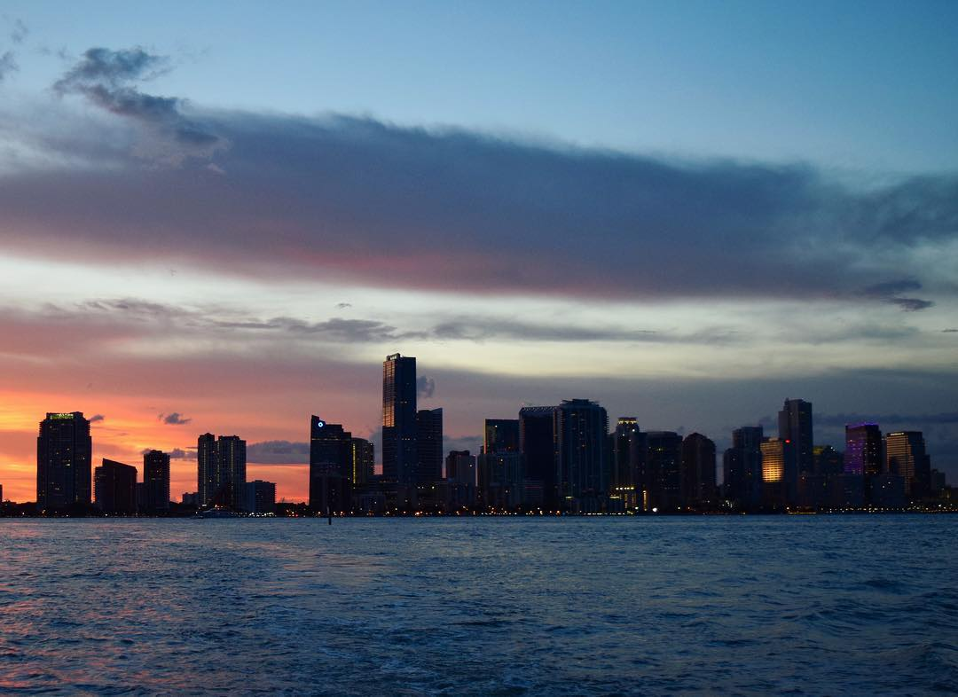 A shot of downtown Miami from the bay as the sun sets, showing orange skies and silhouette buildings