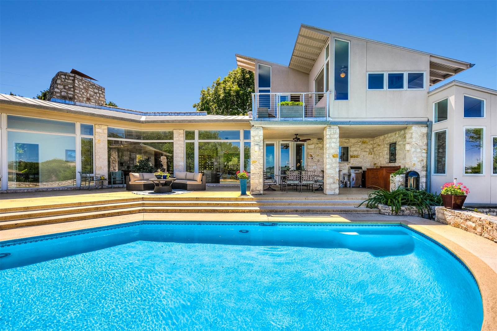 Large muti-leveled contemporary, white, with ground floor wall of windows, pool in front