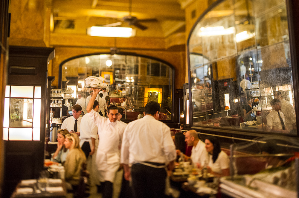 Servers walk around in white in the grand Balthazar dining room, flanked in antiqued mirrors