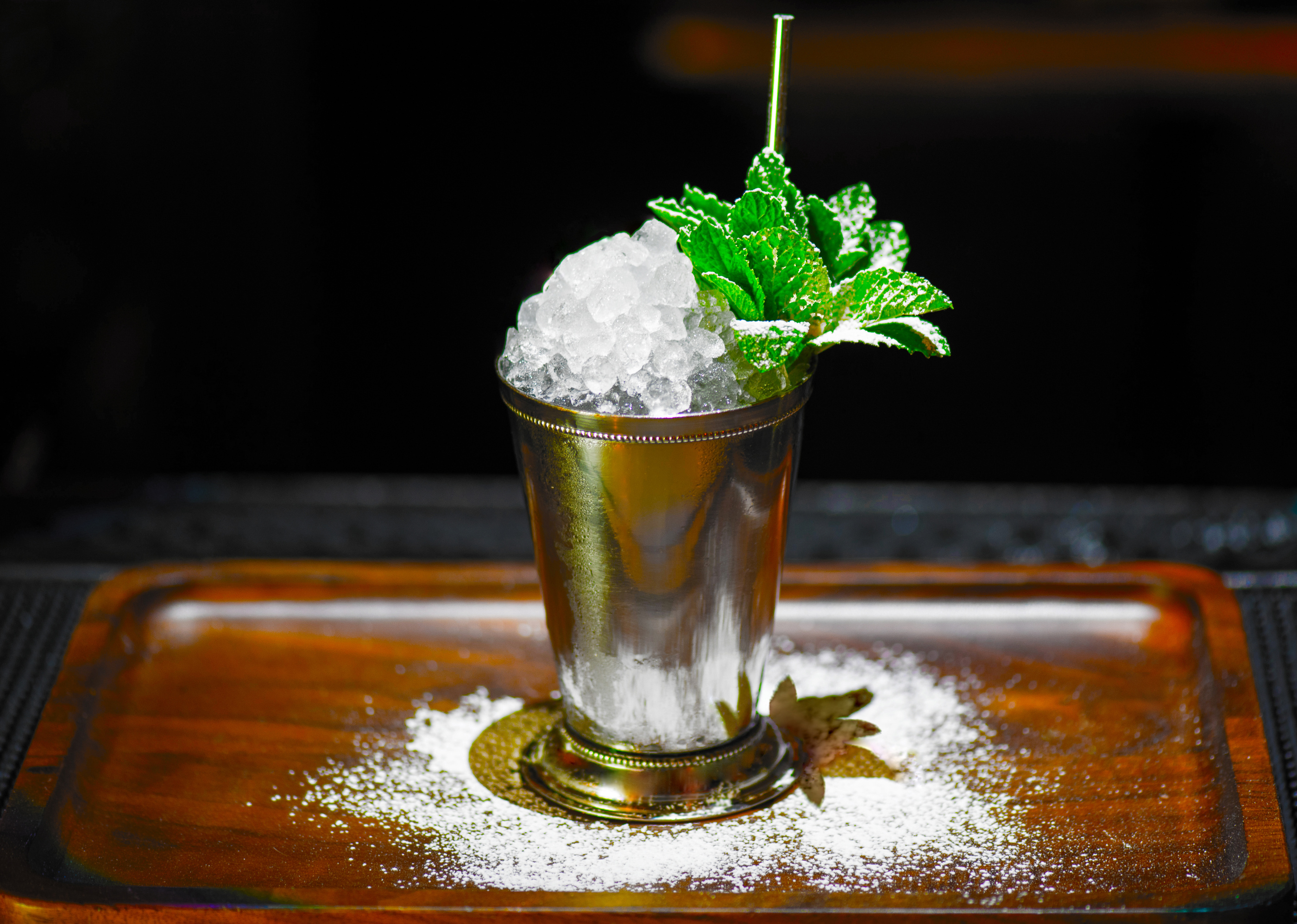 A cocktail in a steel can with a pile of crushed ice and green mint.