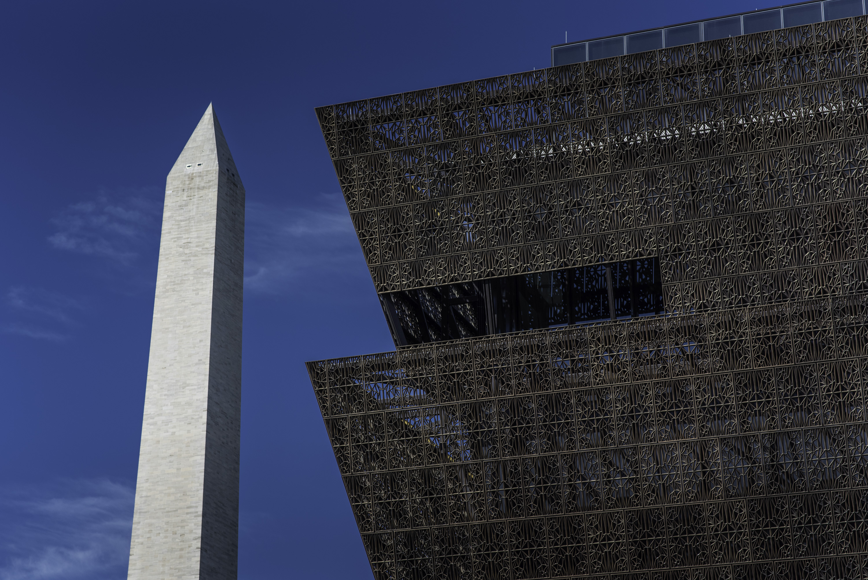Shot of Washington Monument alongside the copper edges of a tiered copper building.