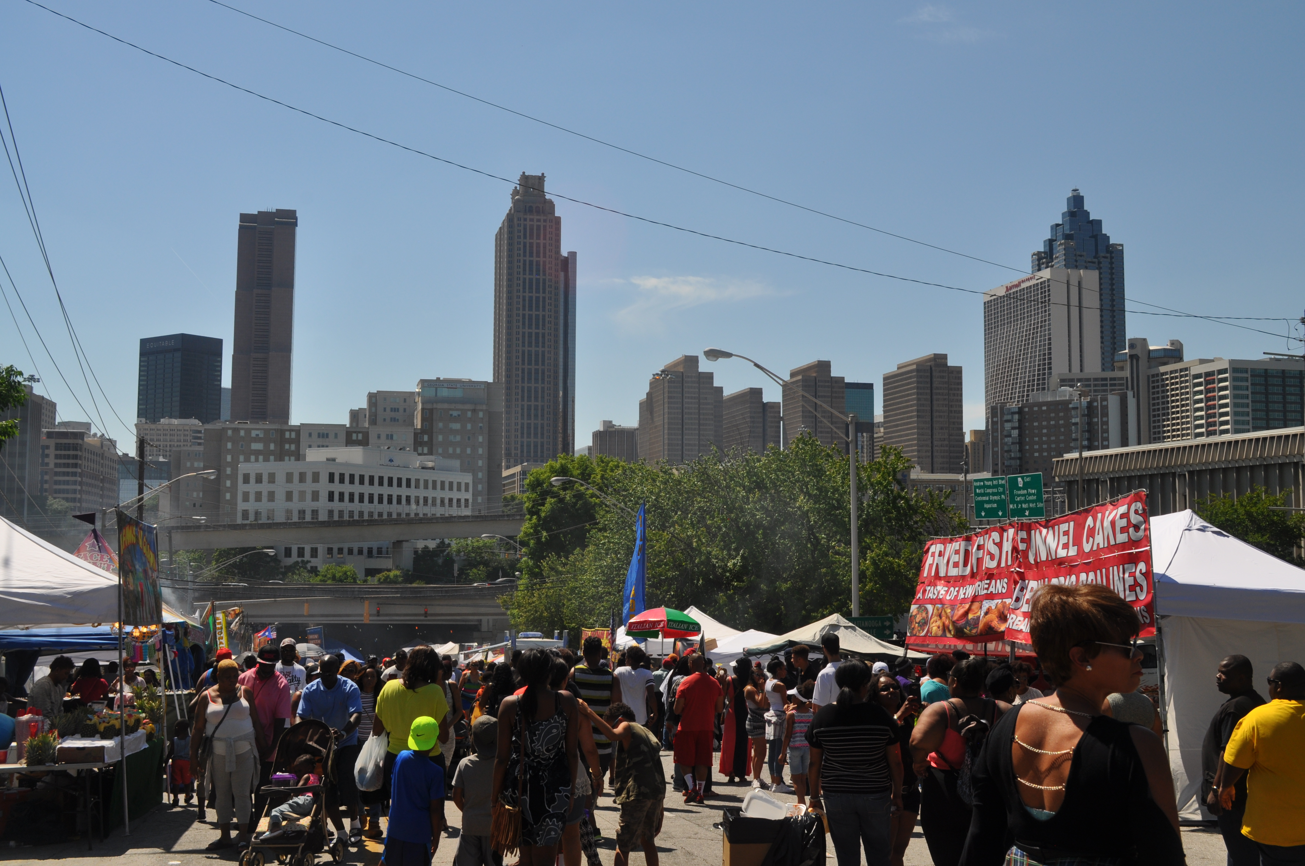 A crowd of people and vendors with downtown skyline beyond.