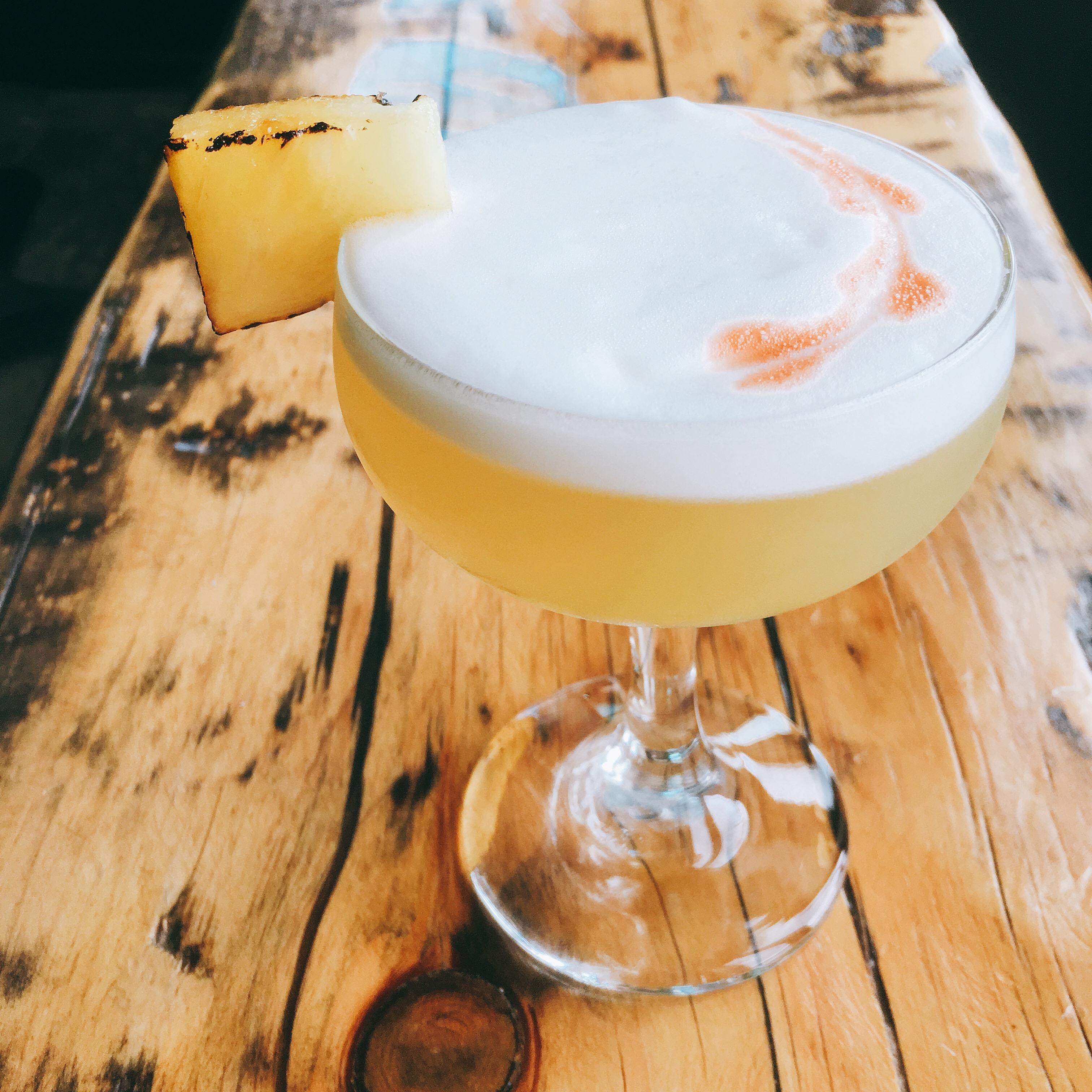 coup with a frothy yellow cocktail garnished with pineapple
