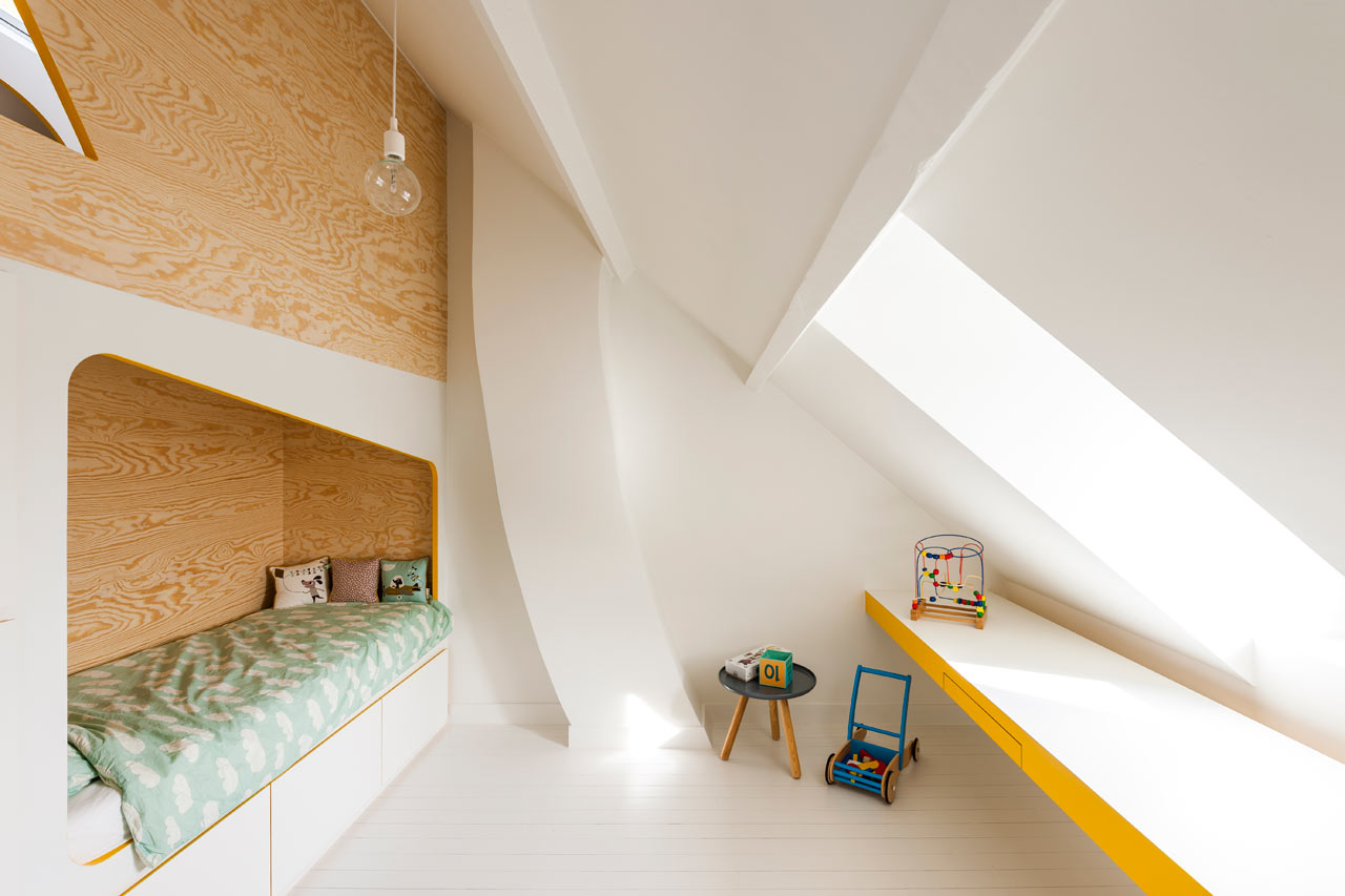 Section of white room with sloped ceilings with a long built-in desk running along wall and a bed within a wooden alcove which is a separate unit and also holds a playhouse above.