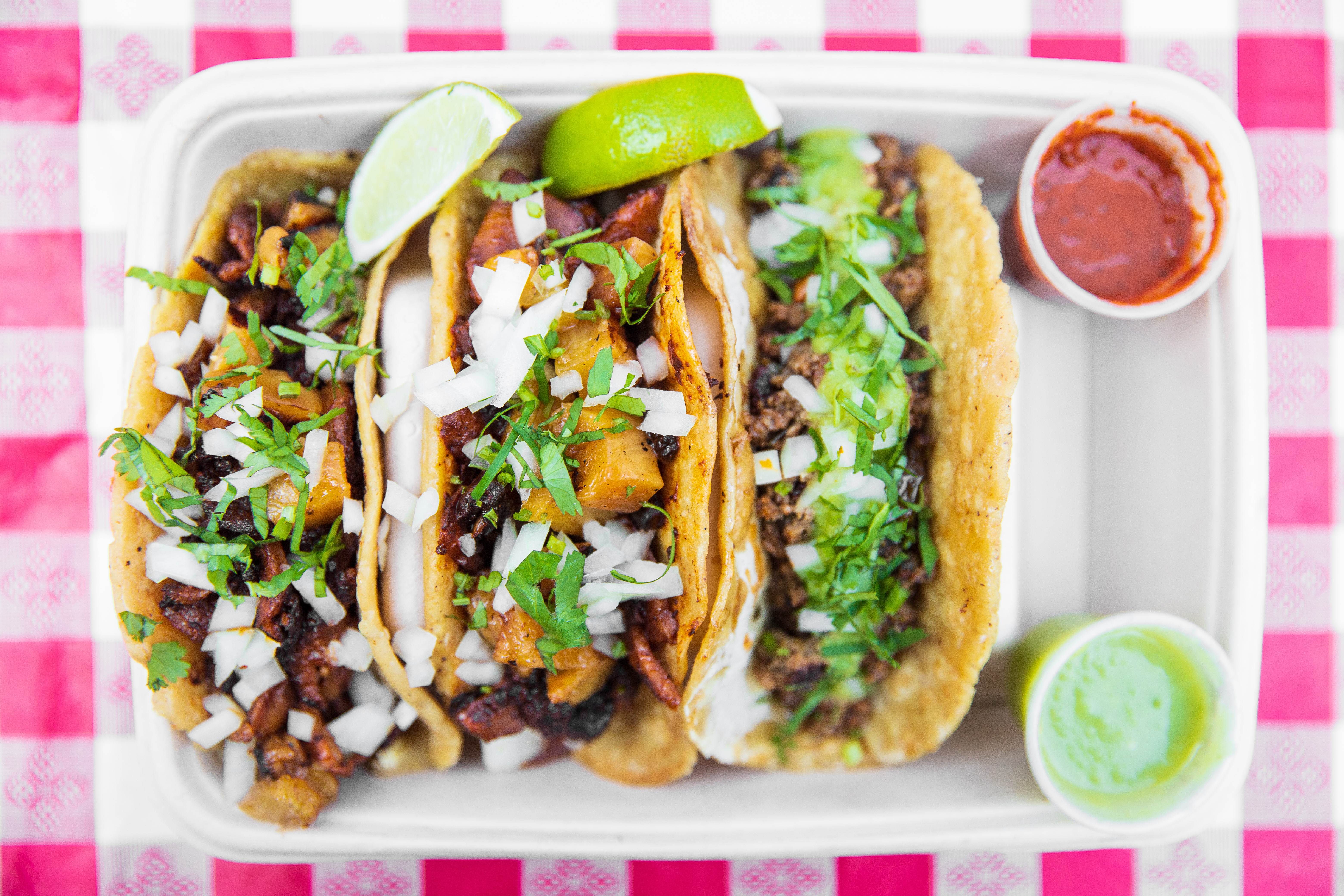 A tray of three tacos with salsas.