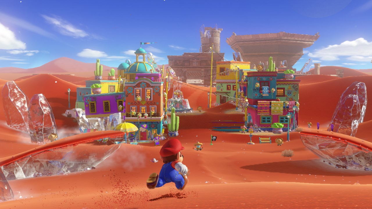 Sand Kingdom in Super Mario Odyssey. Mario is in the foreground running on orange sand. In the distance are a group of very colorful buildings.