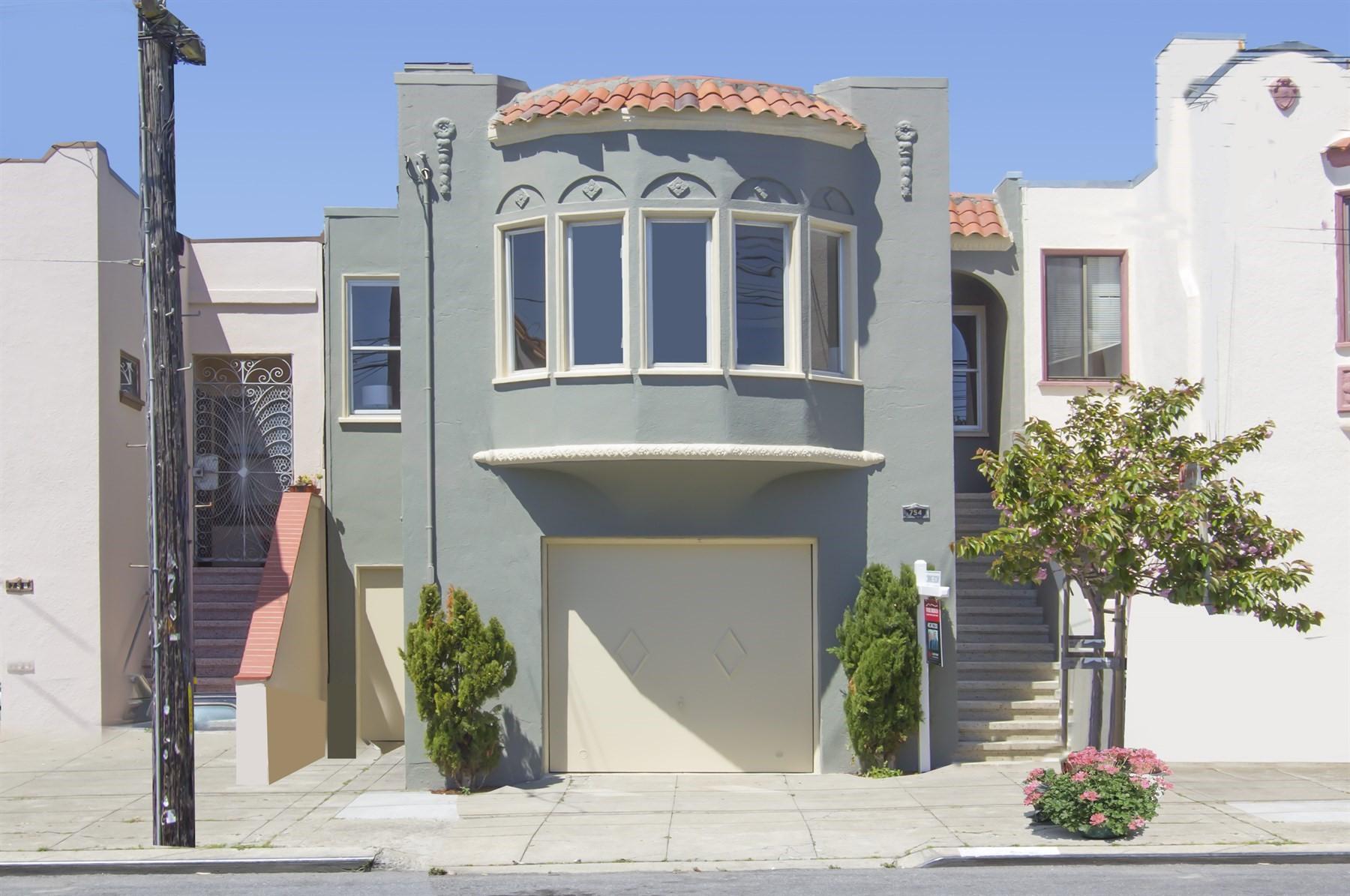 Exterior of 1927 home, gray facade, barrel bay windows.