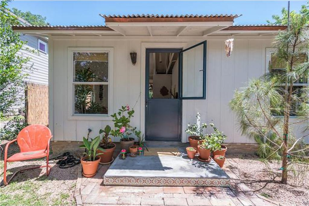 Small white frame home with flat roof and blue dutch door