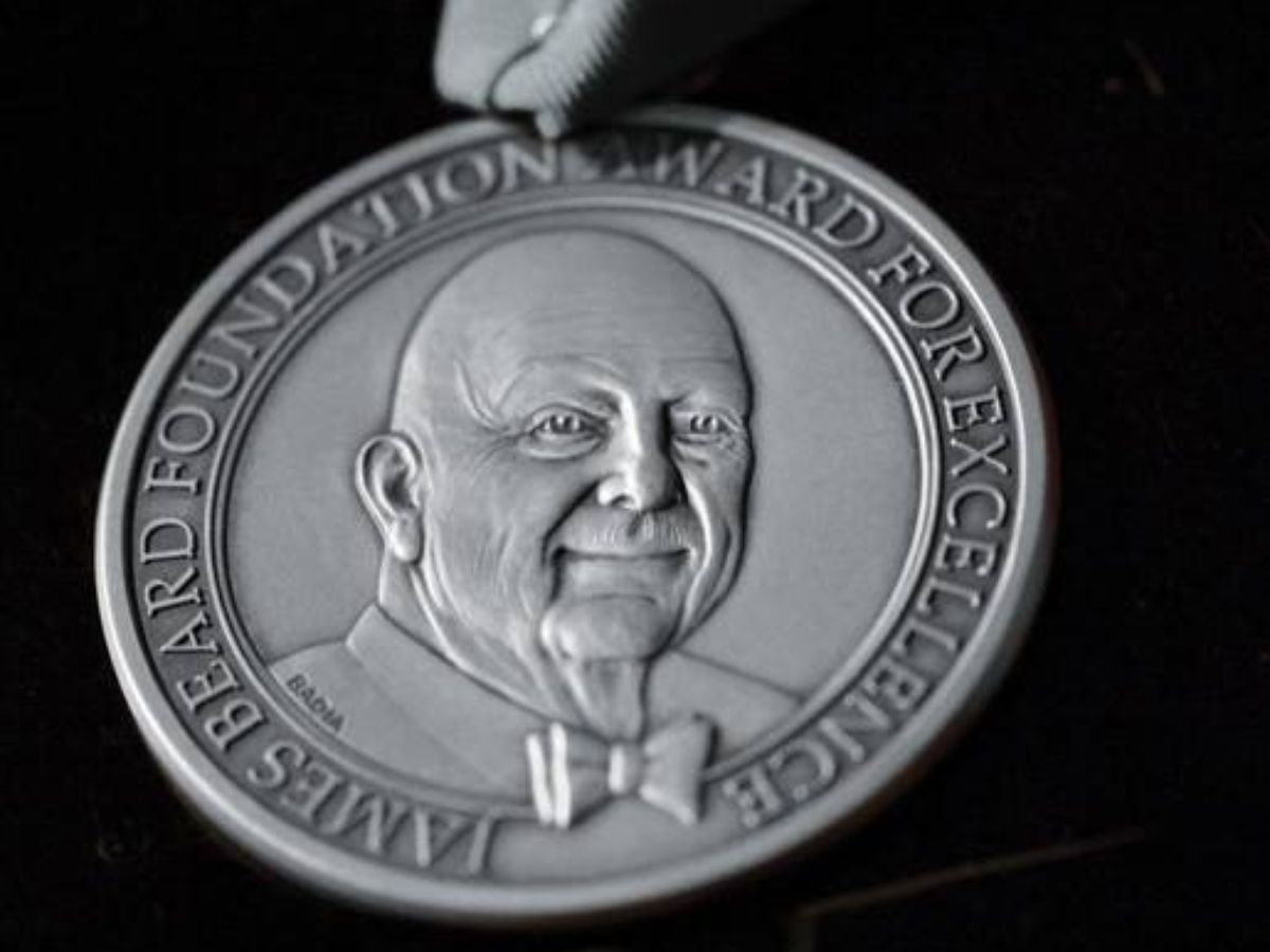 A silver James Beard medal is isolated on a black background