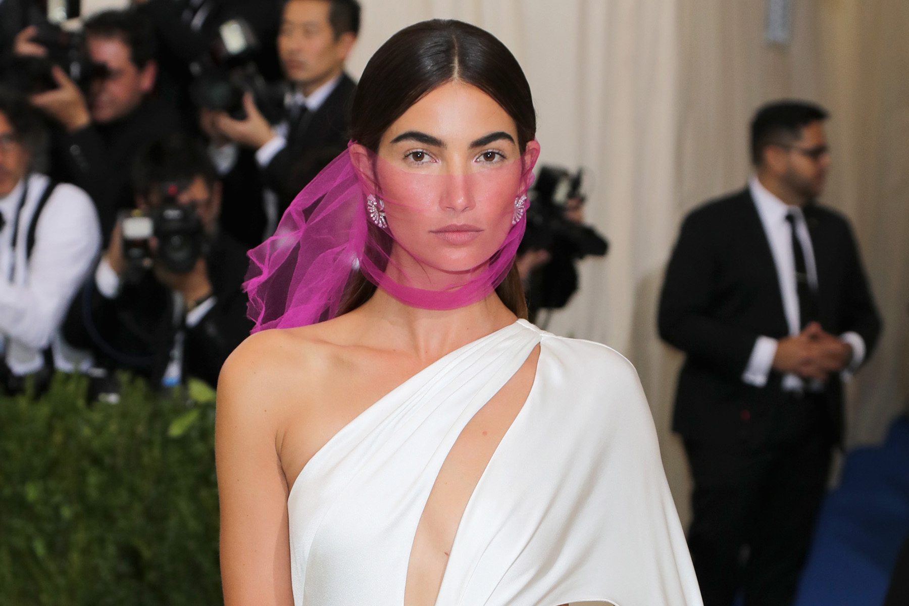 A woman on the red carpet in a white dress and pink scarf