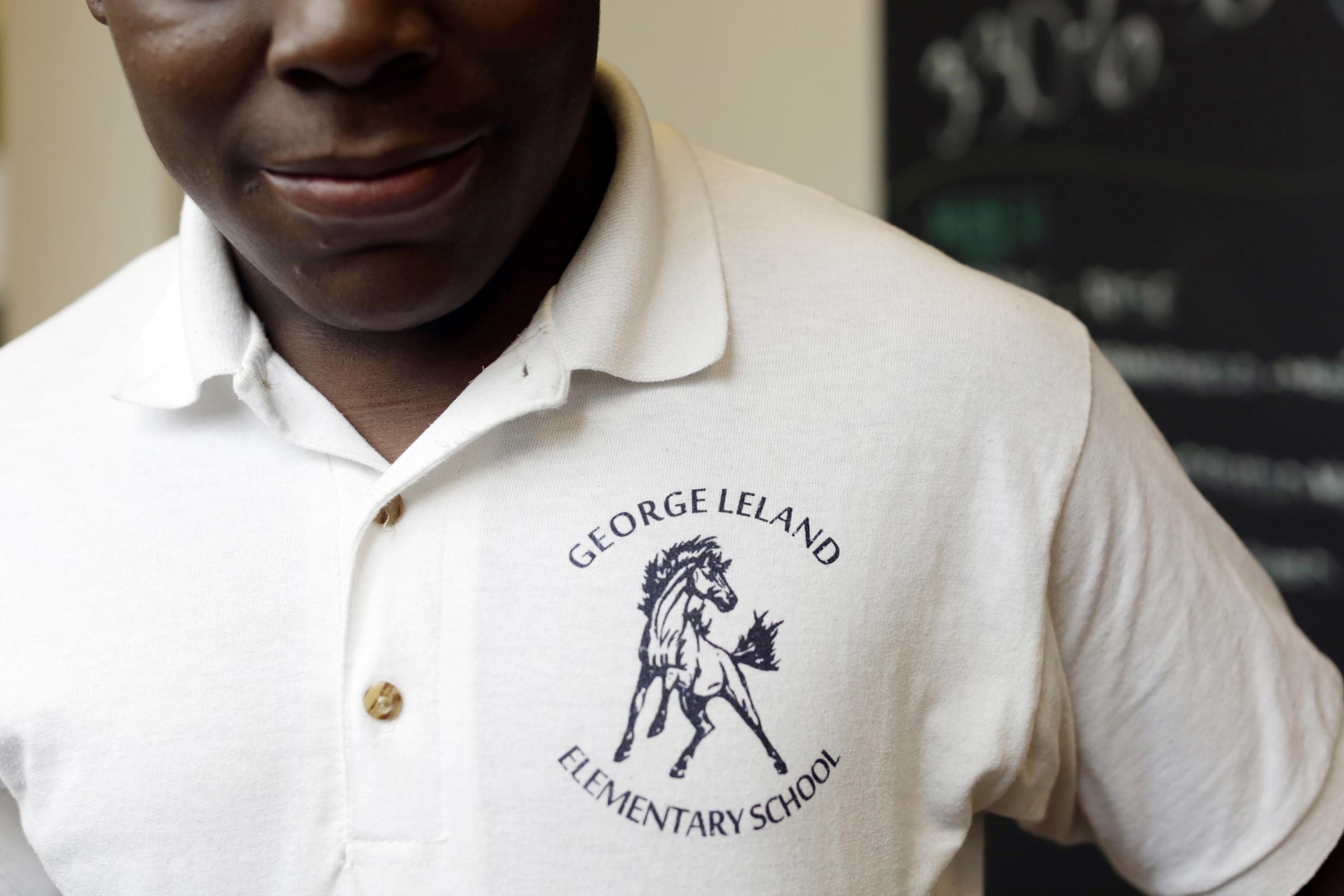 Student Daquian Denton wears a school uniform, a white polo with the logo of George Leland Elementary School.