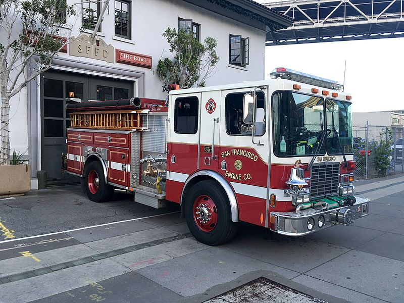 A fire engine pulling out of a garage near the Bay Bridge.