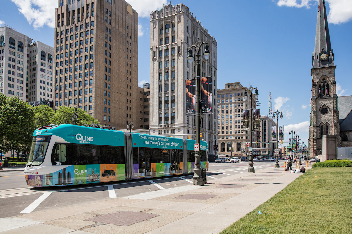A street in Detroit. There is a bus that has a sign that reads: Q Line. There are buildings on both sides of the street.