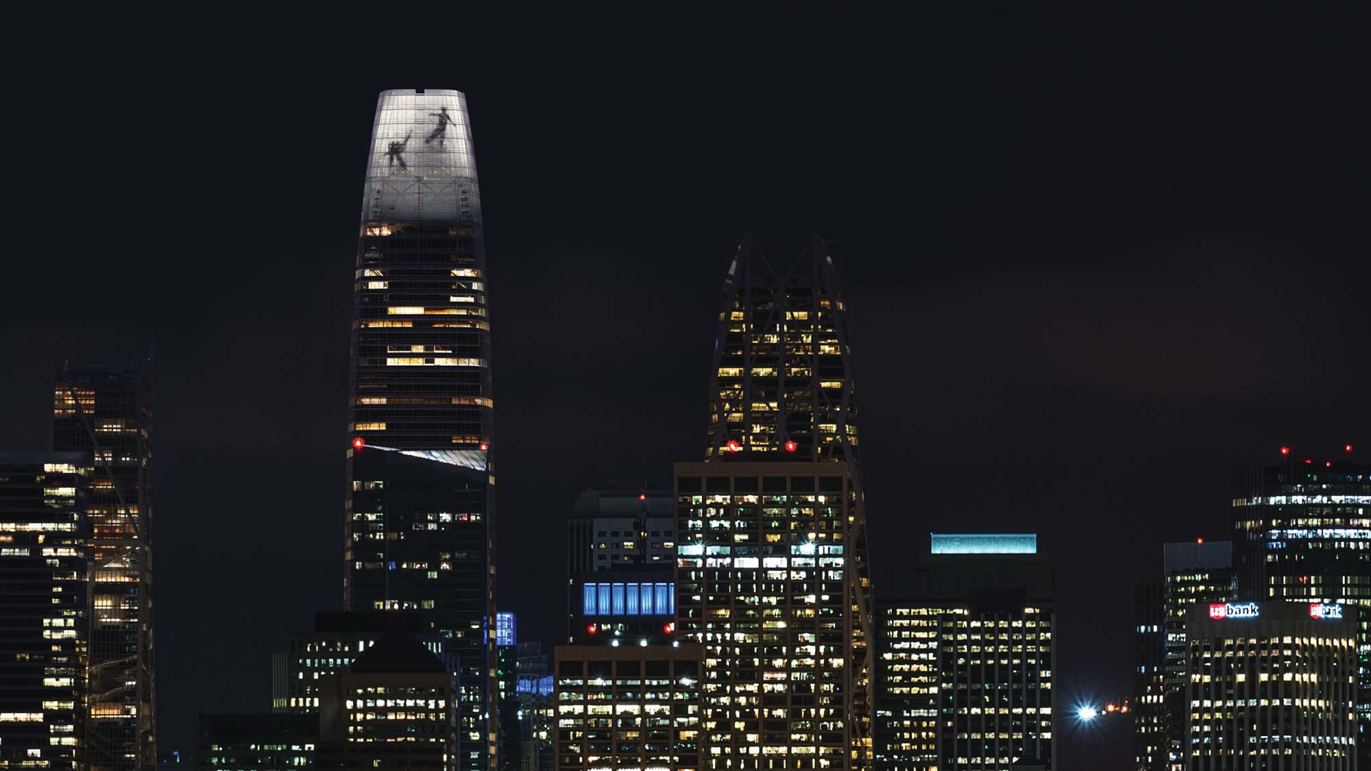 Renderings of human silhouttes dancing in a light display atop Salesforce Tower.