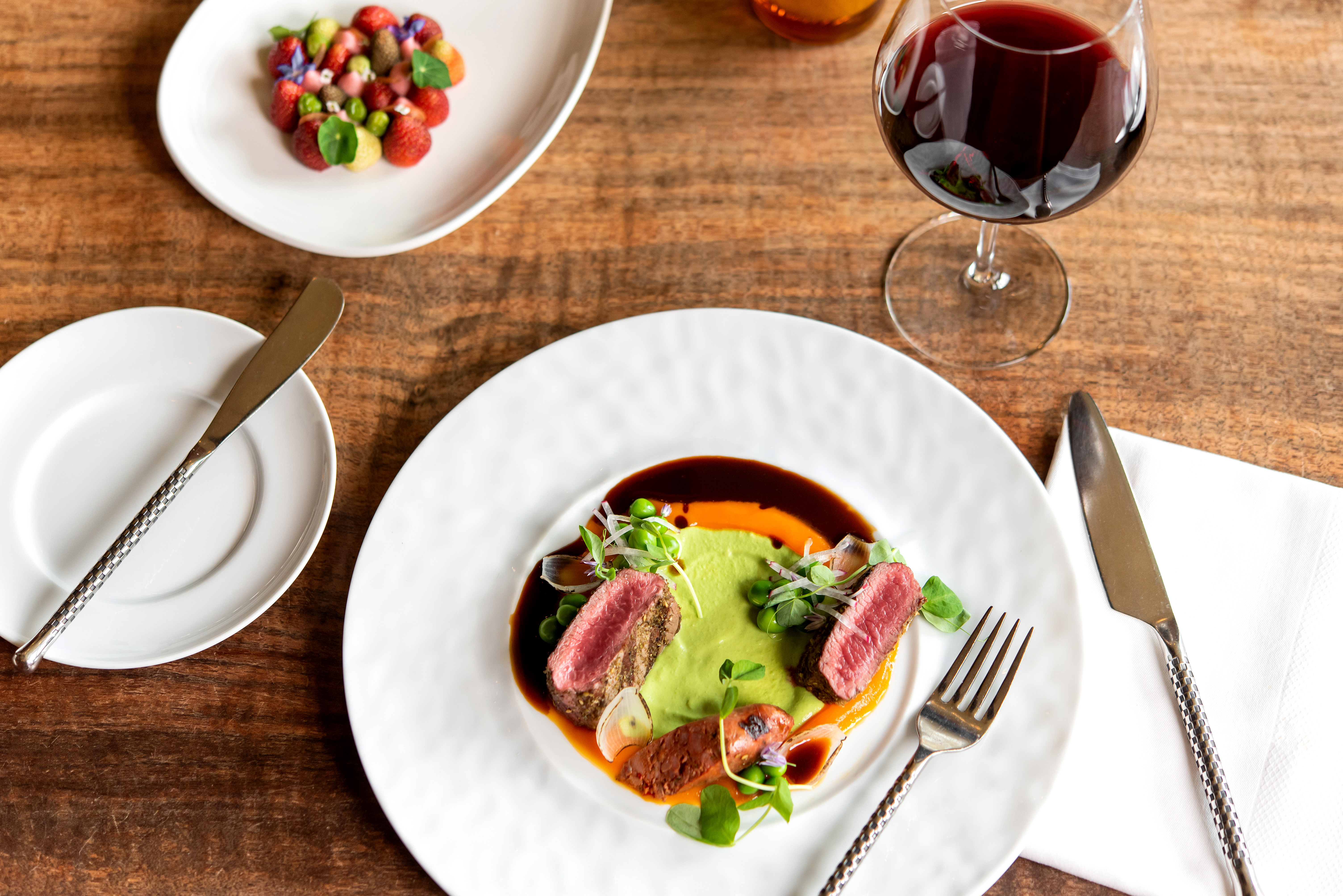 A rare steak, a small vegetable salad, and a glass of pinot noir sit on a table at Jory, the restaurant within the Allison Inn & Spa