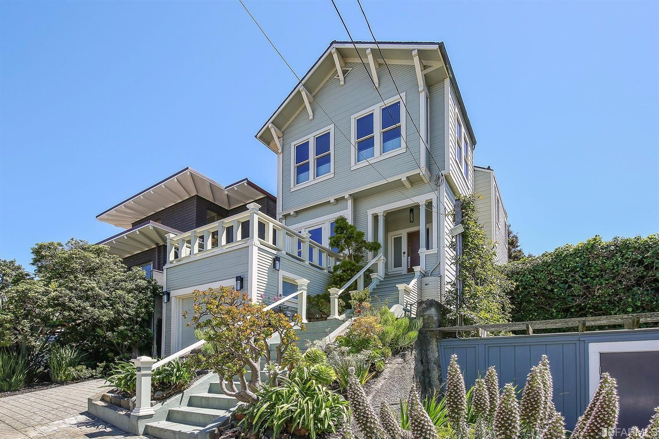 A three-story craftsman home with a deck off the front of the second floor.