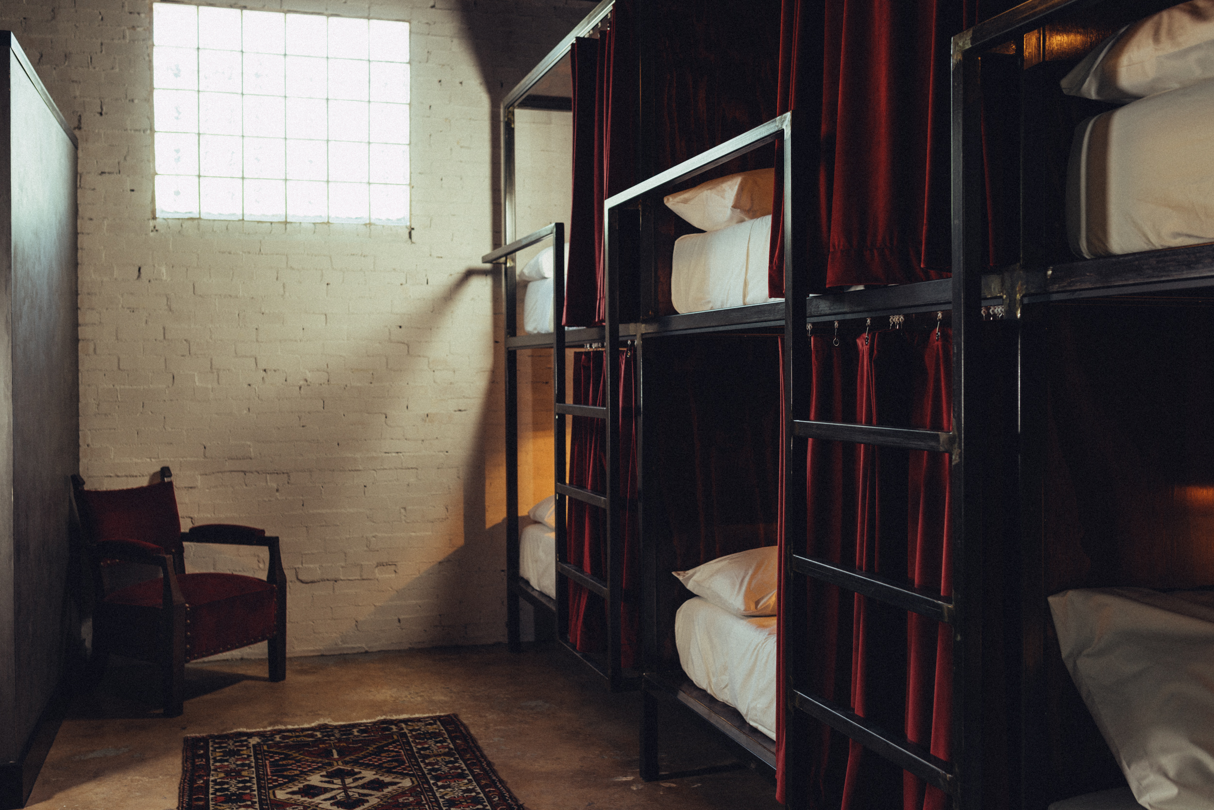 Dimly lit room with fancy bunk beds and a chair in the corner, high window