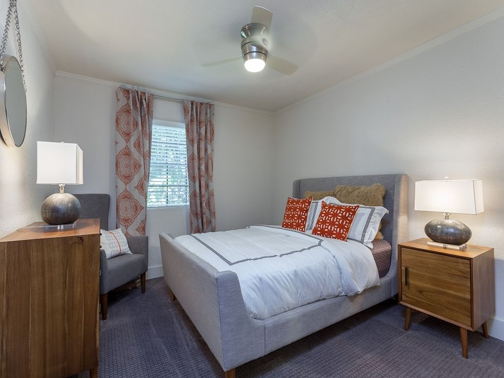 Furnished apartment bedroom with modern furniture, white bedspread, curtains