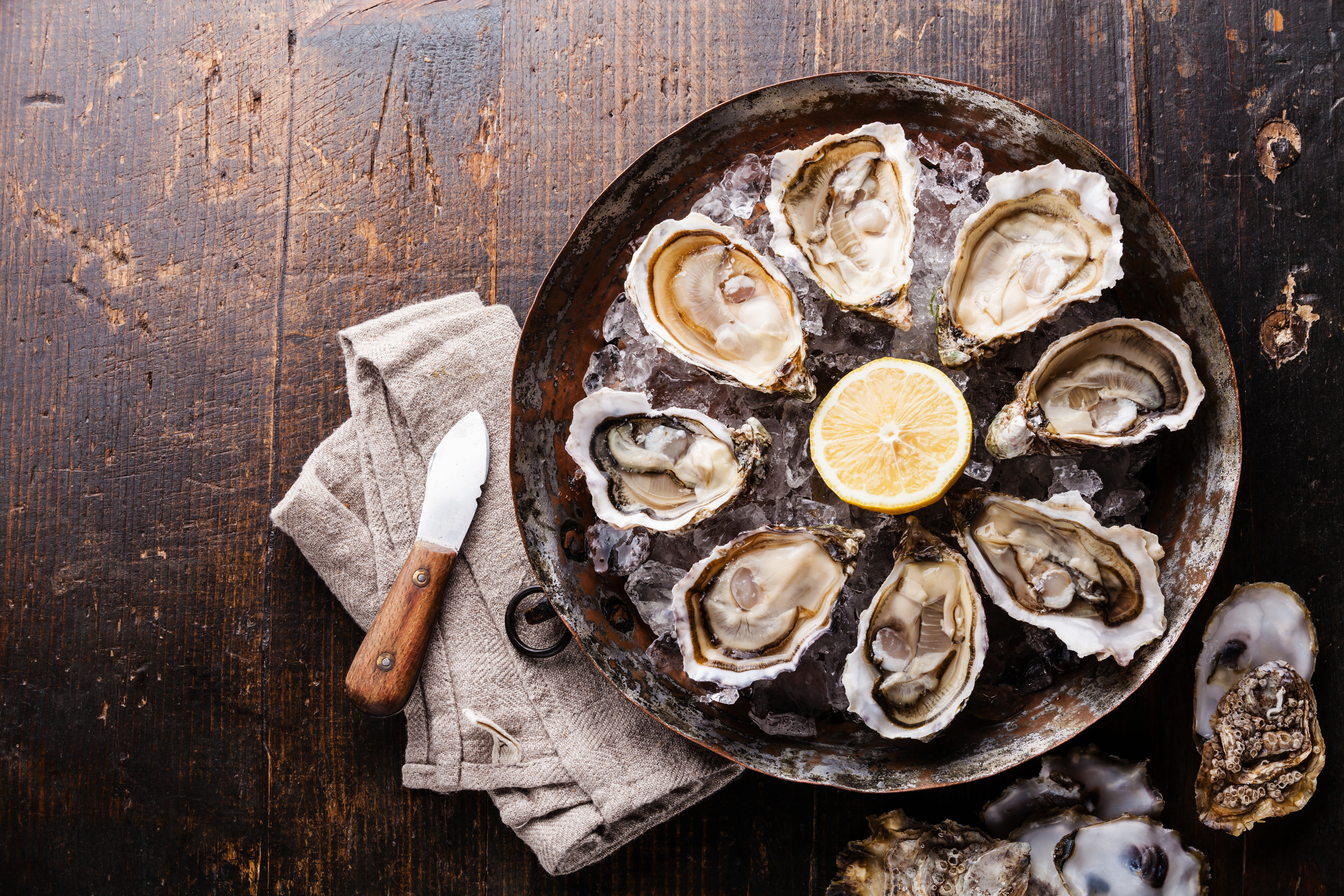 Stock photograph of oysters. An overhead view shows a platter of eight oysters on the half shell on ice, with a sliced lemon in the middle, all sitting on a dark wooden table.