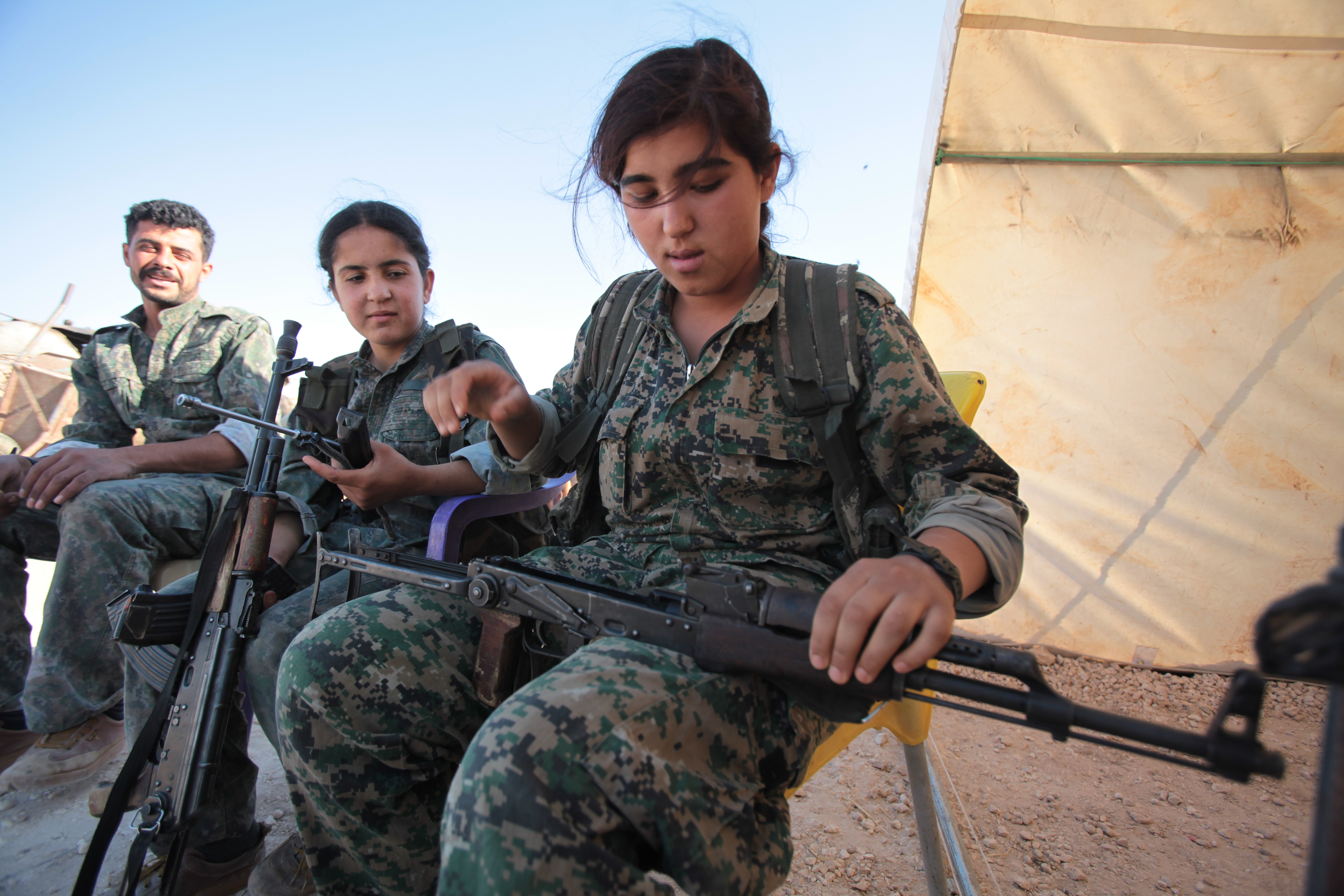 A Kurdish People's Protection Units, or YPG's woman fighter controls her AK-47 in a camp at the outskirts of the destroyed Syrian town of Kobane, also known as Ain al-Arab, Syria.