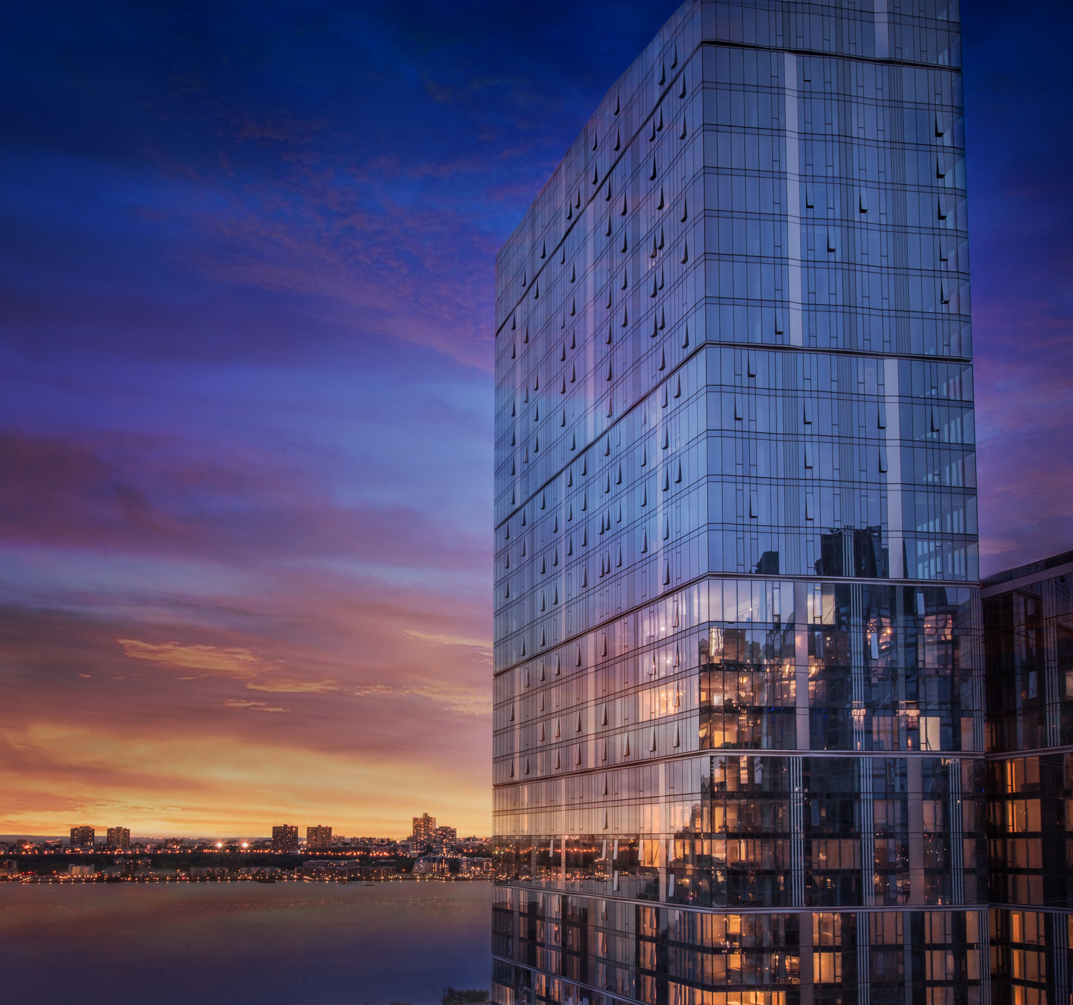 A tall building with a glass facade. There is a colorful sunset in the sky.