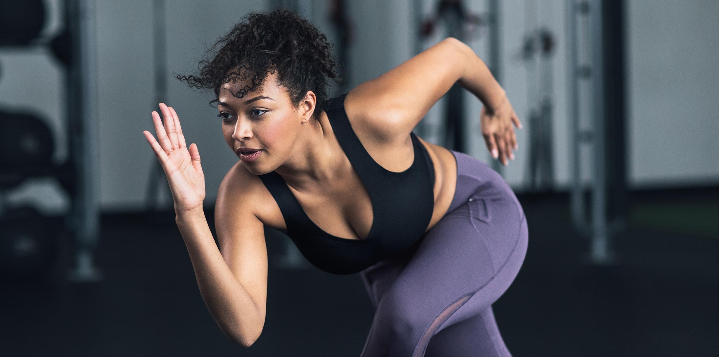 A model wearing a black Lululemon sports bra and purple workout leggings