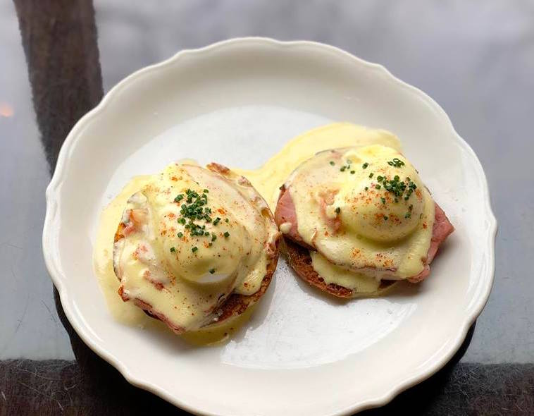 A plate of eggs. Benedict with little pools of pale yellow sauce over the egg domes.