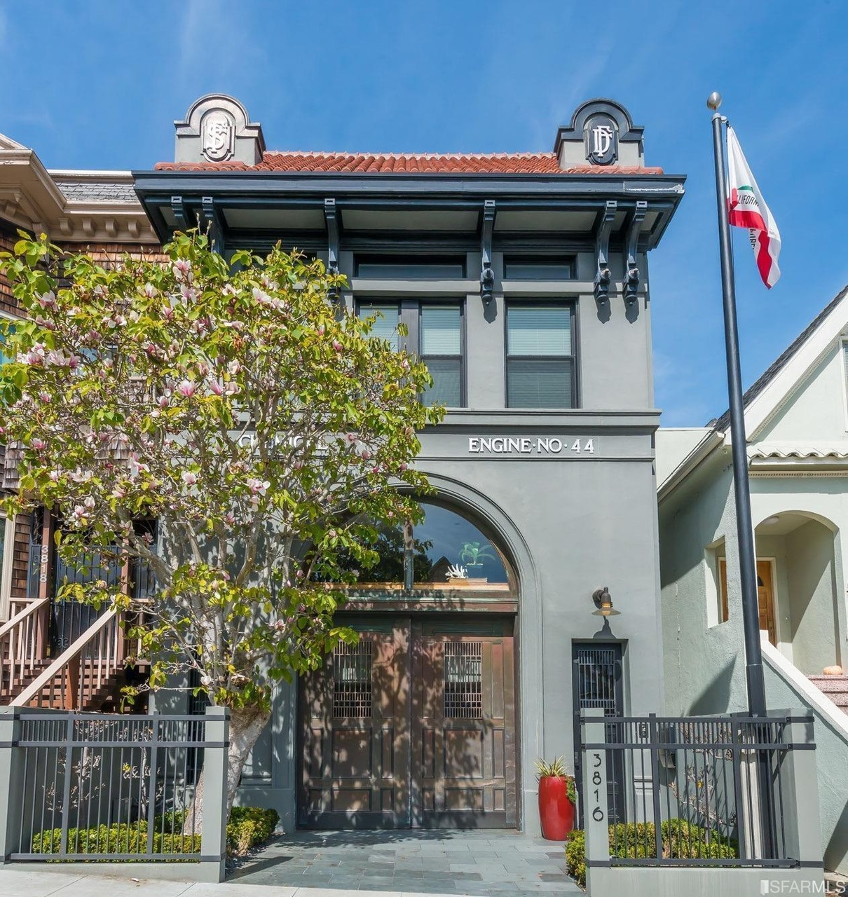 """A former firehouse turned contemporary home, with the words """"Engine No 44"""" still visible on the facade."""