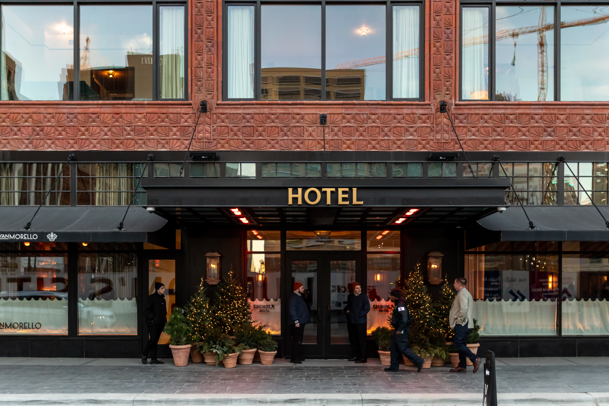 The exterior of the Shinola Hotel in Detroit. There is a black awning over the entrance with the word Hotel on it. The building has a red brick facade.