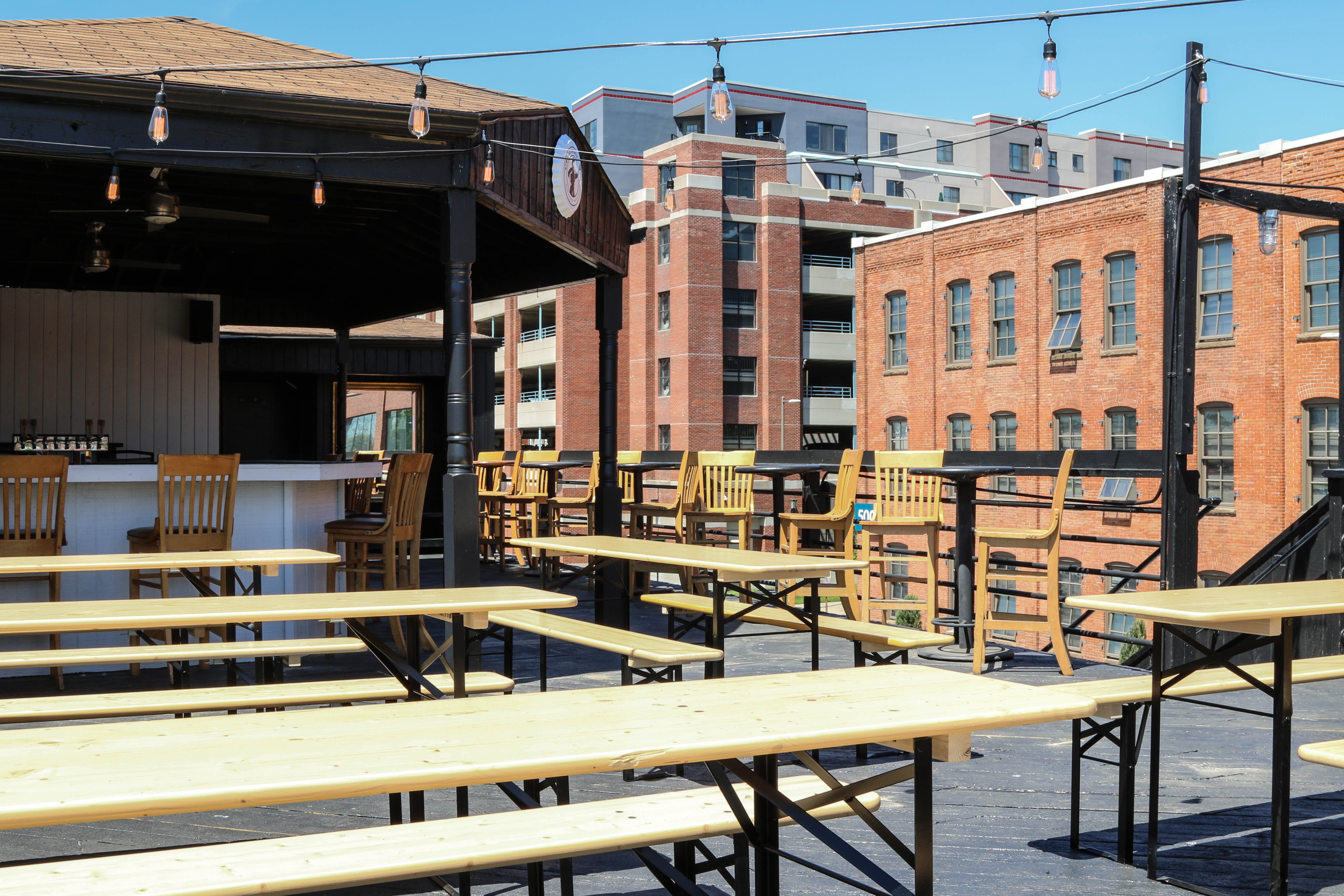 Several long wooden picnic tables accompanied by benches atop a rooftop that has a bar with chairs in the background. Two midrise buildings are in view.