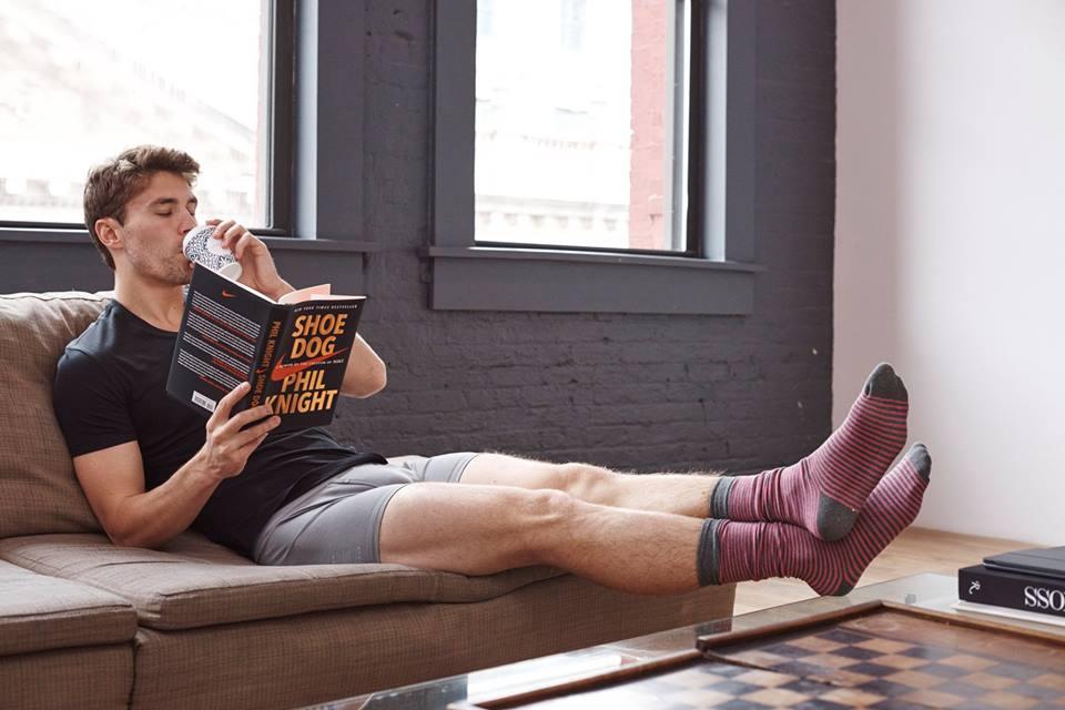 Man in underwear reading a book