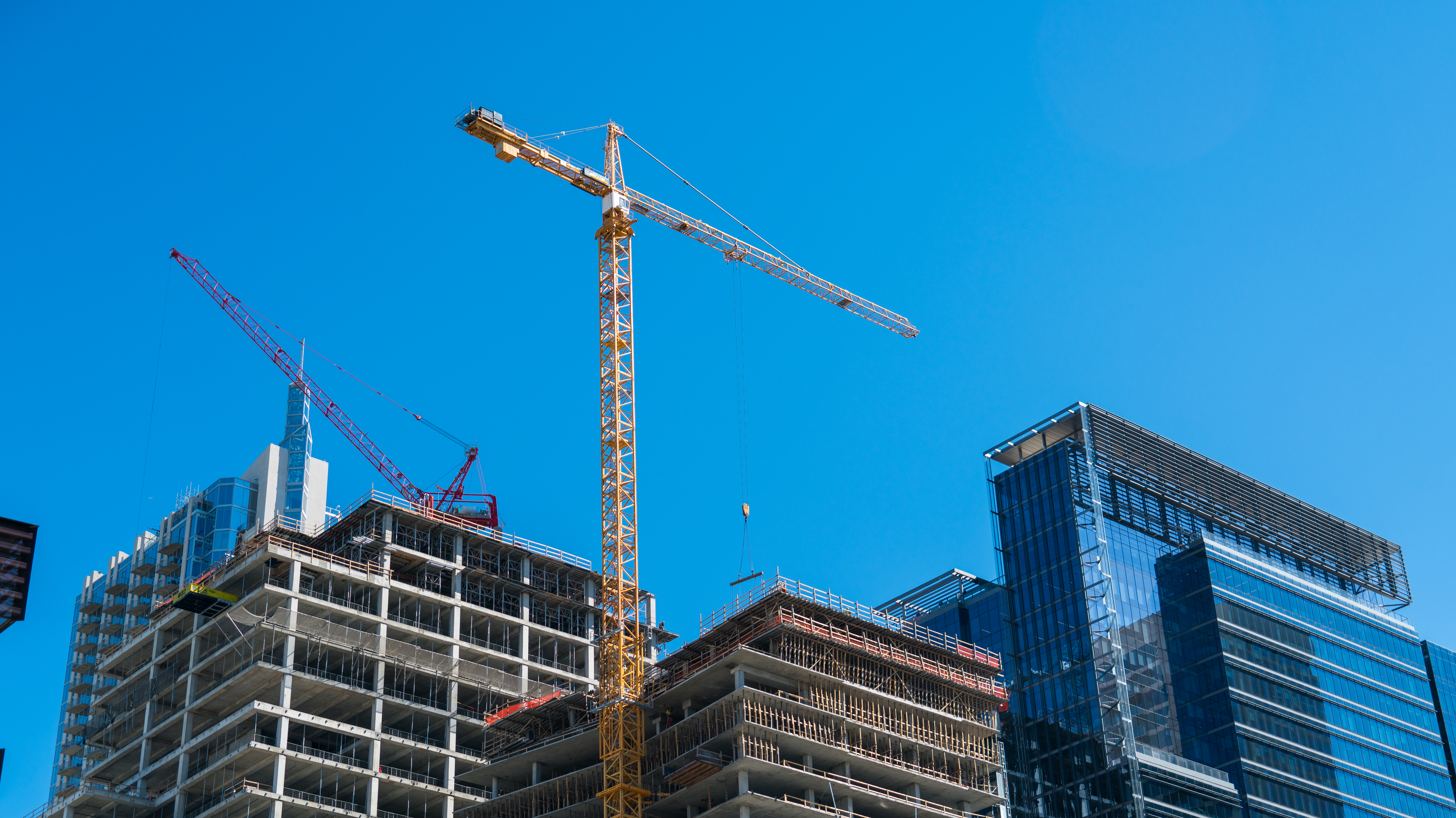 Perfect blue sky day rising modern architecture development Austin Texas Cranes and new Downtown Construction Highrises