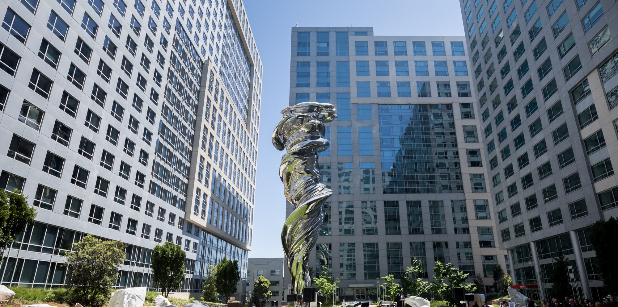 A nine-story silvery statue of a woman surrounded by mid-rise buildings.