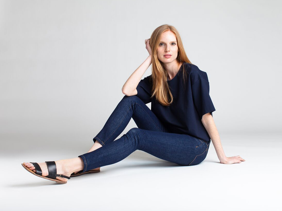 A model wearing dark denim jeans and a blue top