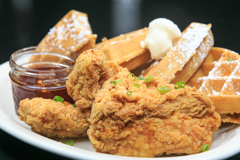 Several crispy pieces of fried chicken are in the foreground of the photo, with four pieces of powdered sugar-covered Belgian waffles in the back
