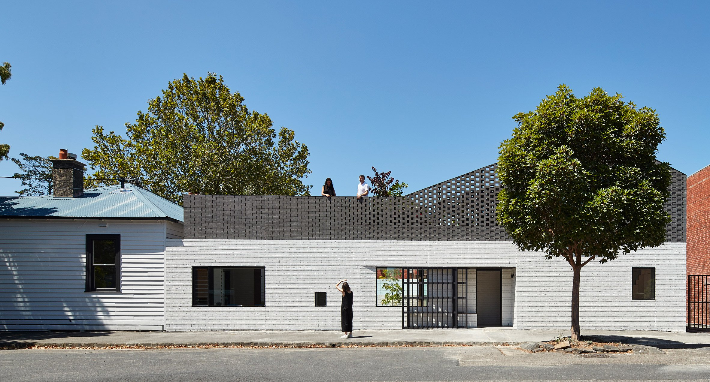 External shot of side of house made up of a small wooden cottage and a long brick extension with a lower half painted white brick and the top floor clad in black-painted brick with a screen that peaks on the far end.