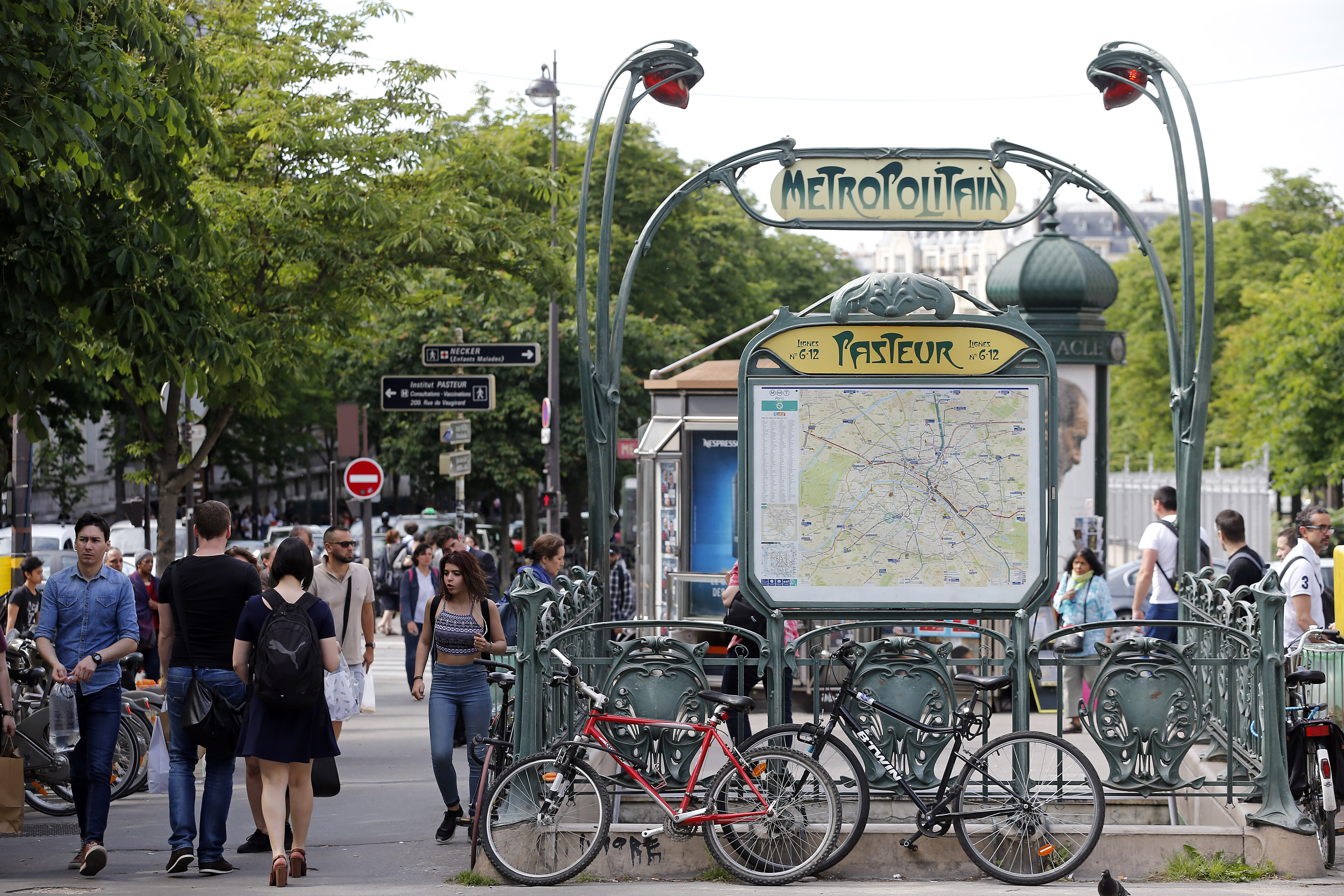 Exterior shot to entrance of Paris subway station. Bikes and passengers are surrounding the green iron entrance.