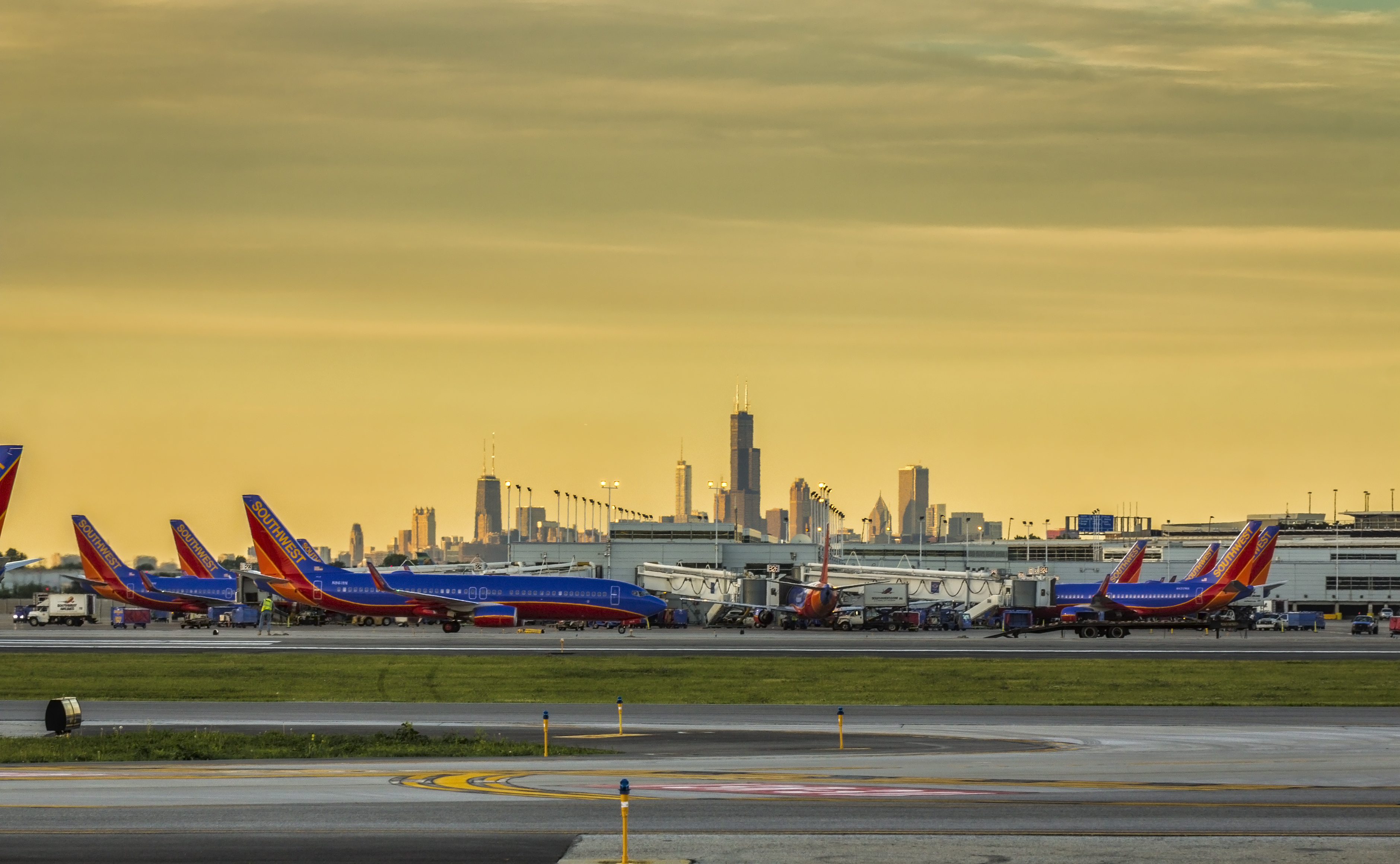 Planes parked at Midway International Airport with the city's skyline in the background.