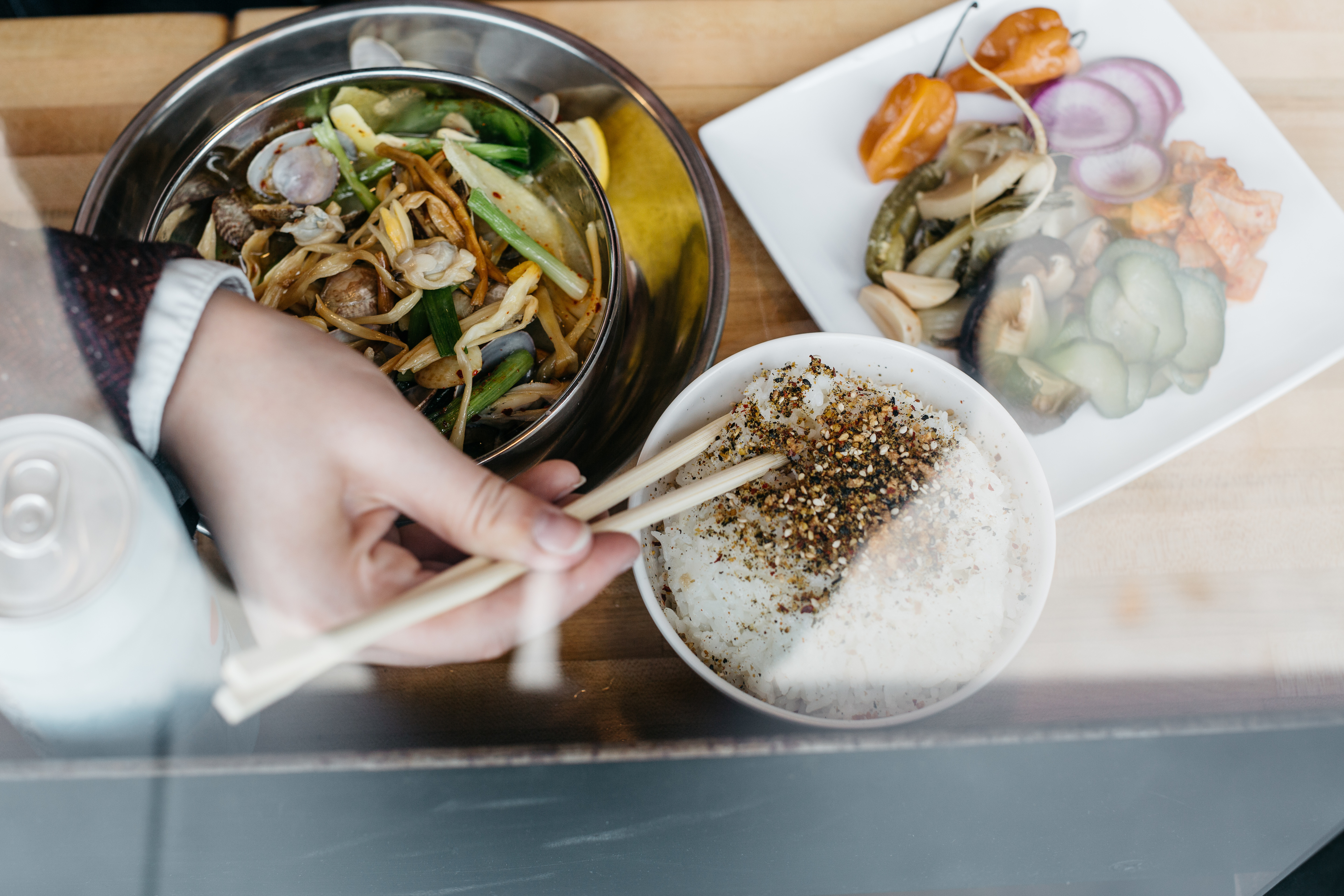 A hand with chopsticks reaches for furikake rice next to a metal bowl of clams and a plate of pickled veggies.