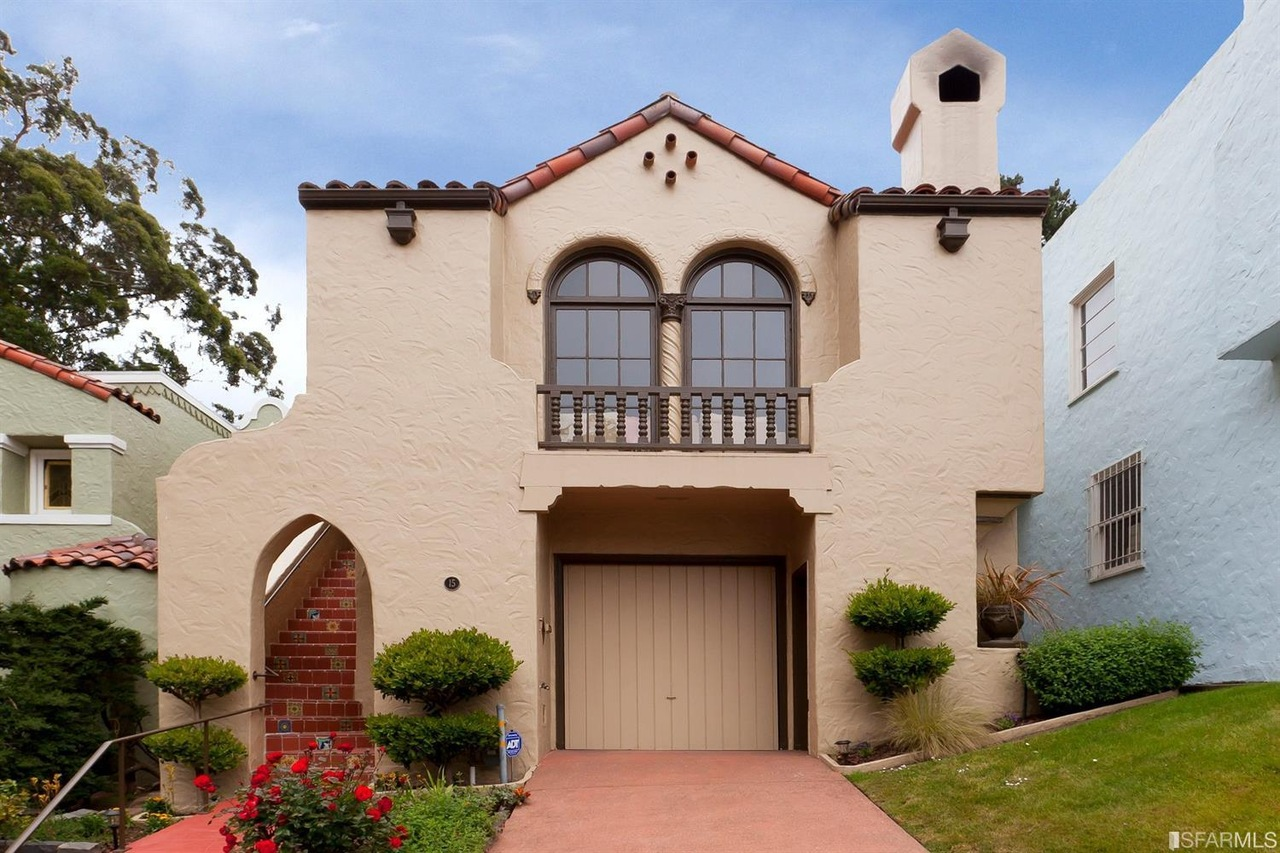 A Spanish-style home with arched windows, a tile roof, and elevated porch.