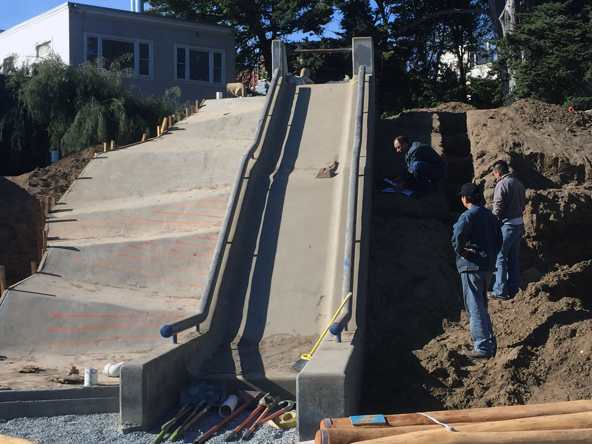 Workers rebuilding the playground's concrete slide.
