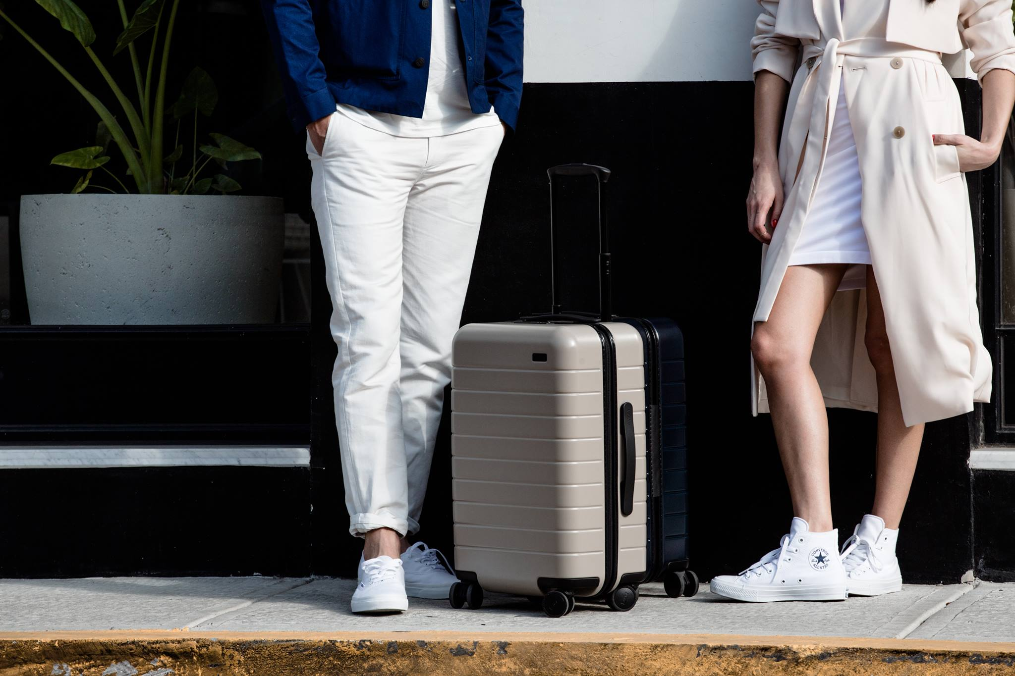 A man and a woman, shown from the waist down, standing near a carry on suitcase