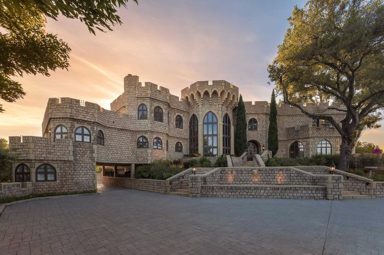 A Silicon Valley home that looks like a castle, complete with Gothic windows and a central tower with crenellations.