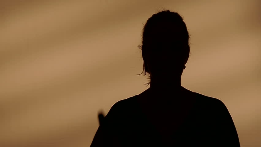 A silhouette of a woman being interviewed by somebody.