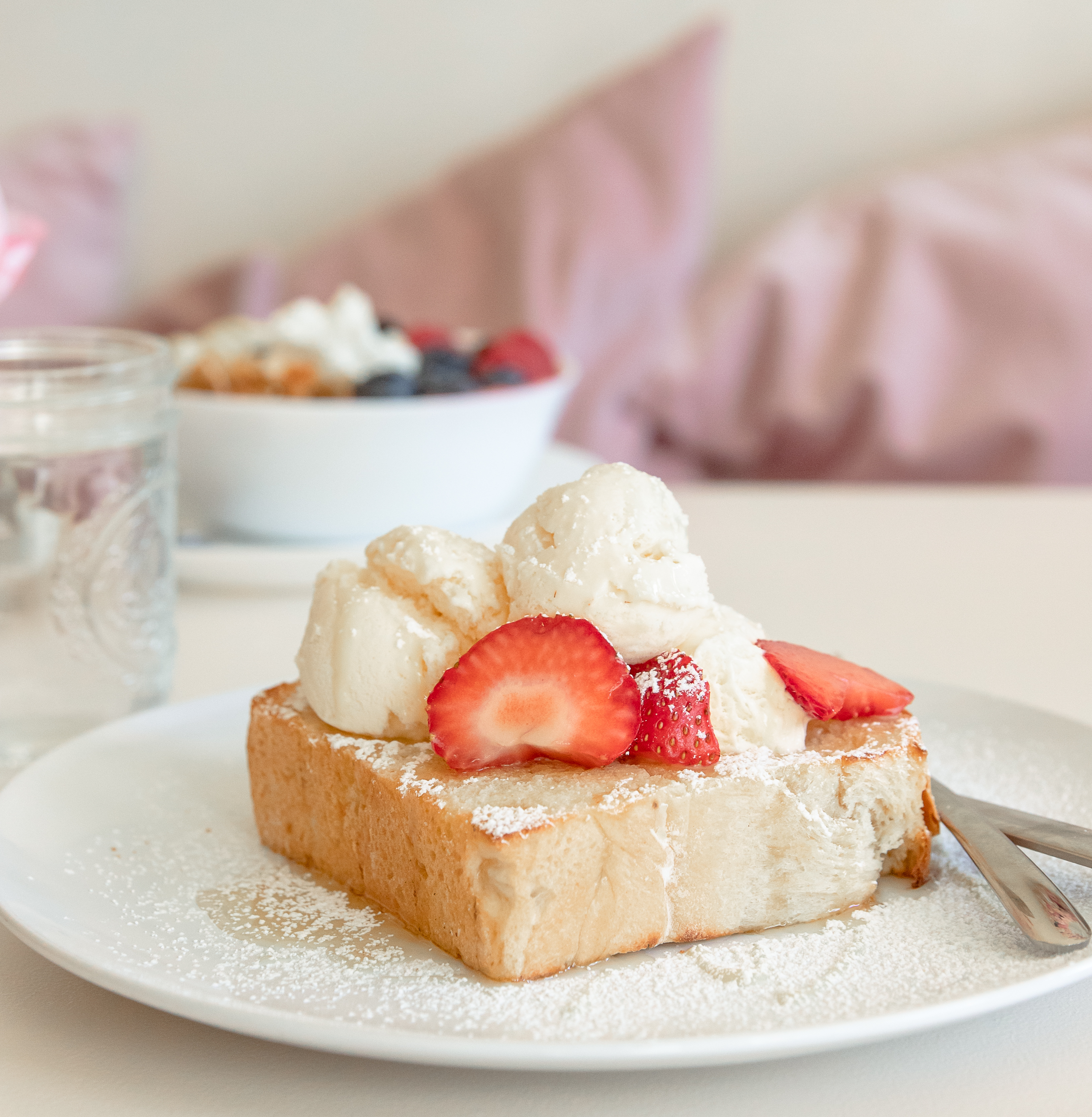 Thick slice of white bread topped with ice cream, strawberries, and a drizzle of honey
