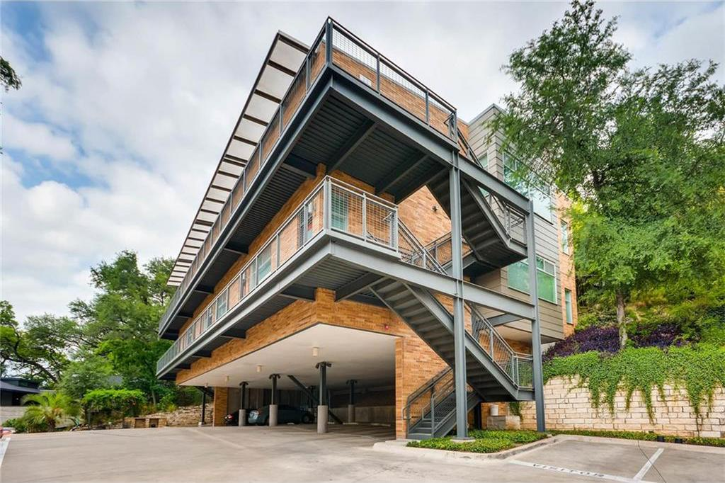 Two-story brick condos with parking below, steel railings and overhang