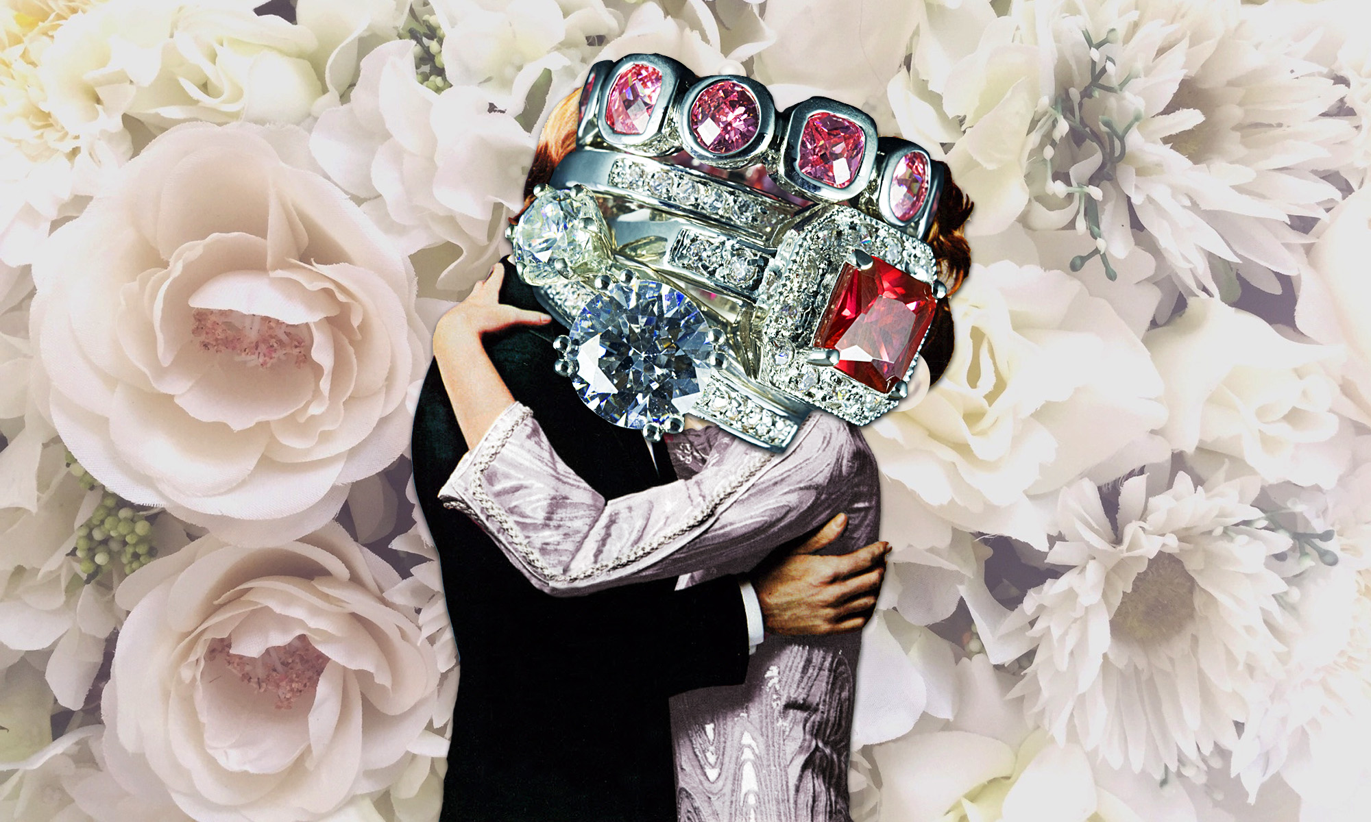 A couple kisses in front of a floral background with a stack of diamond and ruby rings in front of their faces