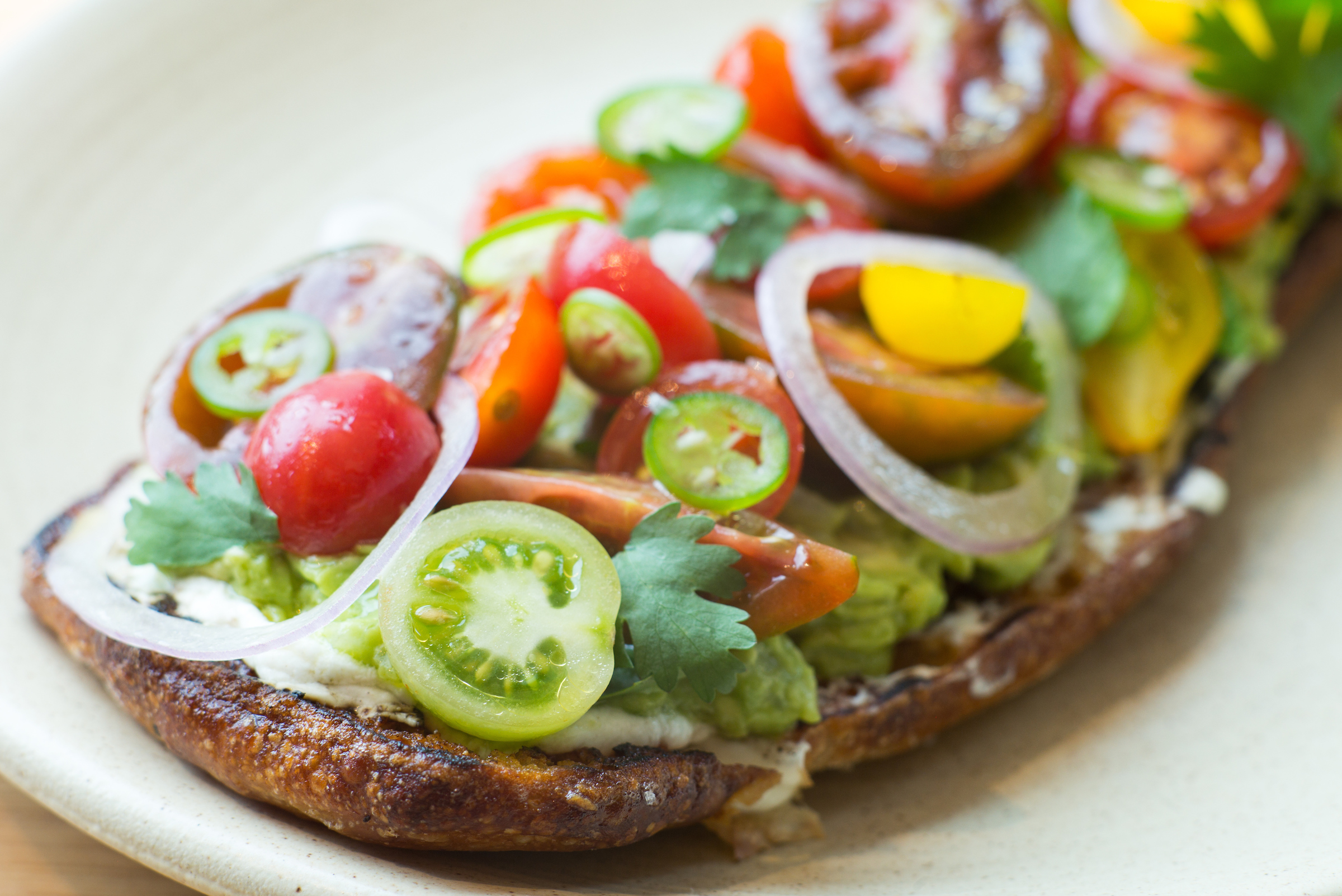 A piece of toasted thickly heaped with colorful cherry tomatoes cut in half, onions, and avocado.