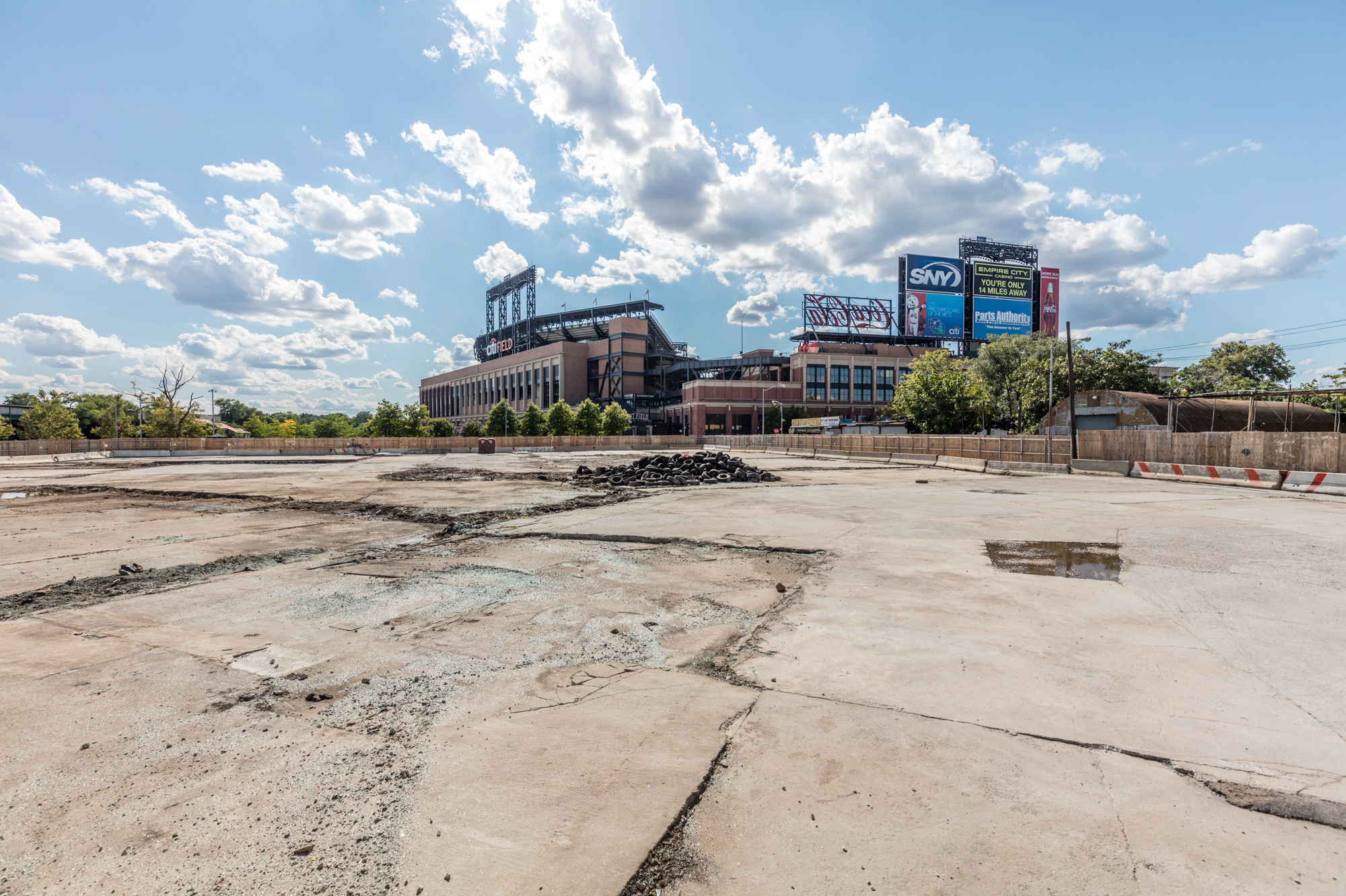 In the foreground is an empty lot. In the distance is a sports stadium.